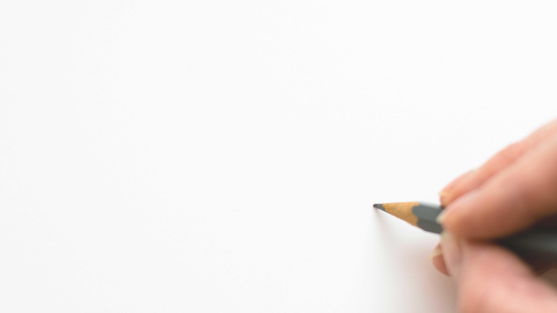 Folha de papel em branco com uma mão segurando um lápis no canto inferior direito da página
