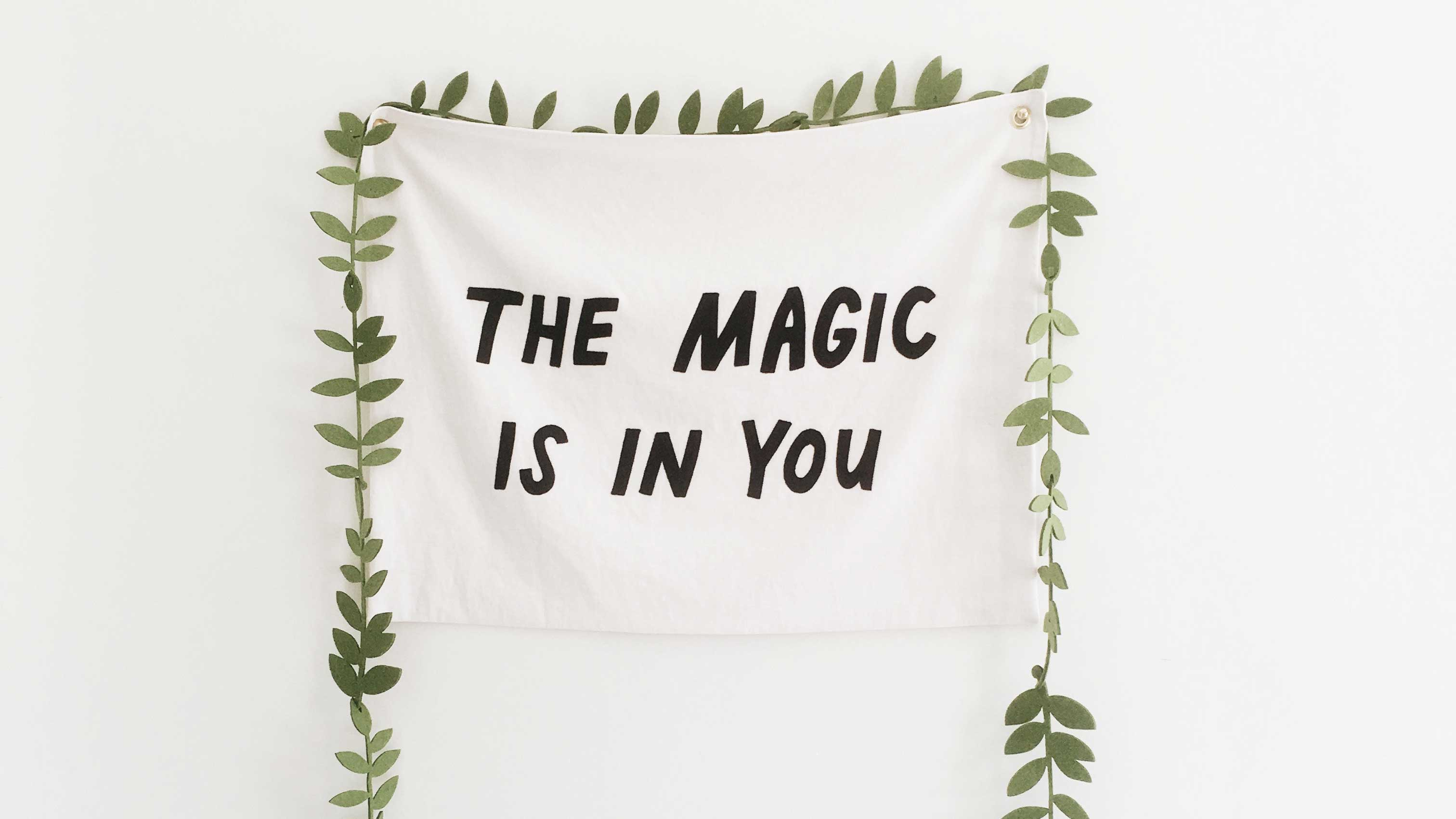 "Pano com a frase ""Tha Magic is in You"" pregado a parede com folhas ao redor, como as de uma árvore."
