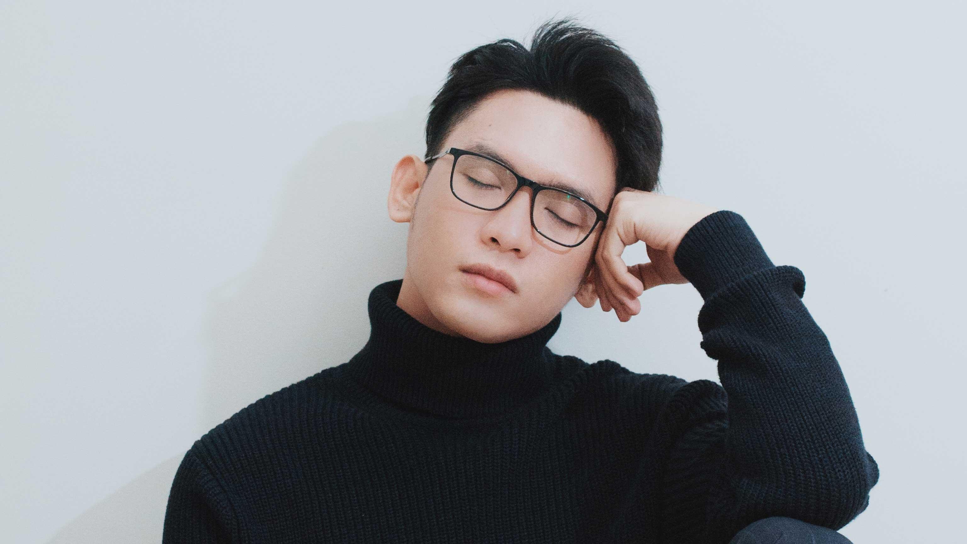 Rapaz de óculos cochilando sentado com a cabeça apoiada no braço.
