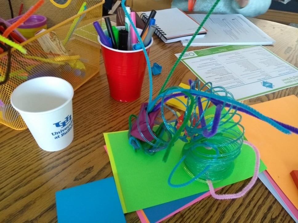 Mesa com papéis, canetas, borracha e alguns brinquedos como molas espalahas