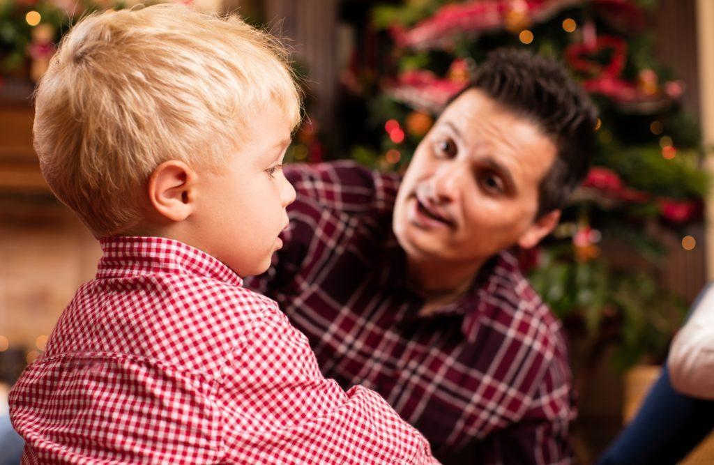 Na imagem temos um homem, aparentemente pai, tentando falar com um menino pequeno de cara emburrada.