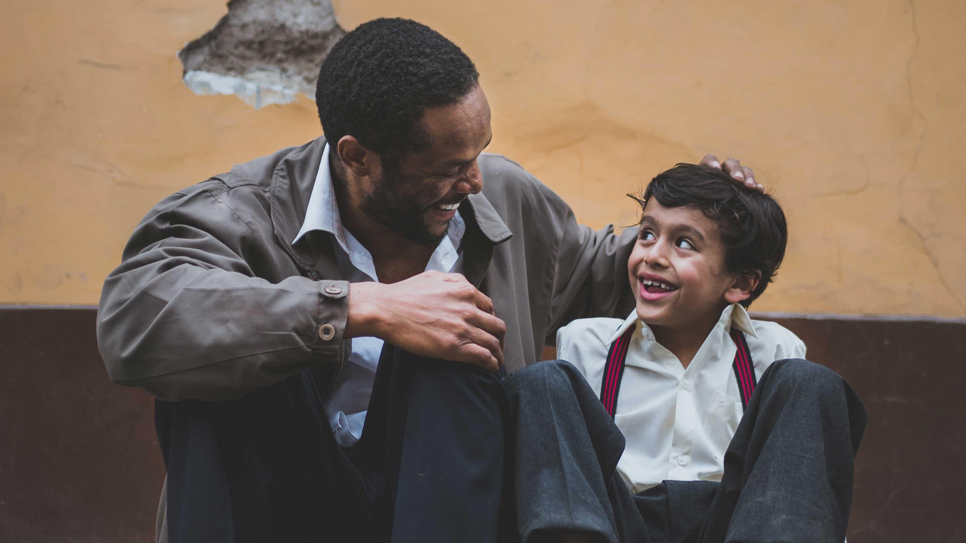 Pai e filho sentados na calçada como se estivessem conversando.