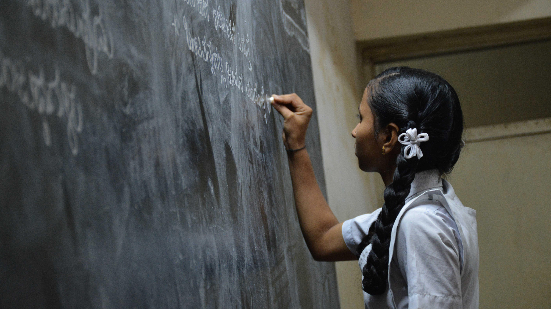 3 Dicas para Driblar a Dificuldade de Aprendizagem das Crianças - Garota de tranças em frente ao quadro negro