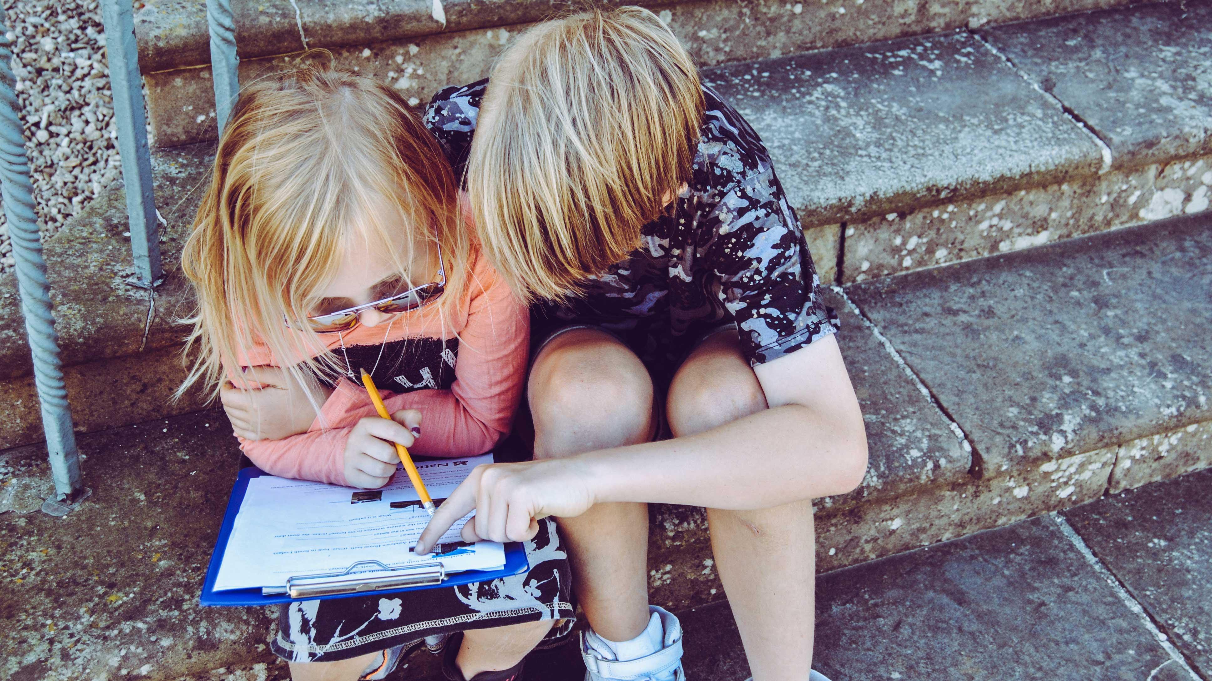 Duas crianças sentadas na escada, o menino ajuda a menina com uma lição