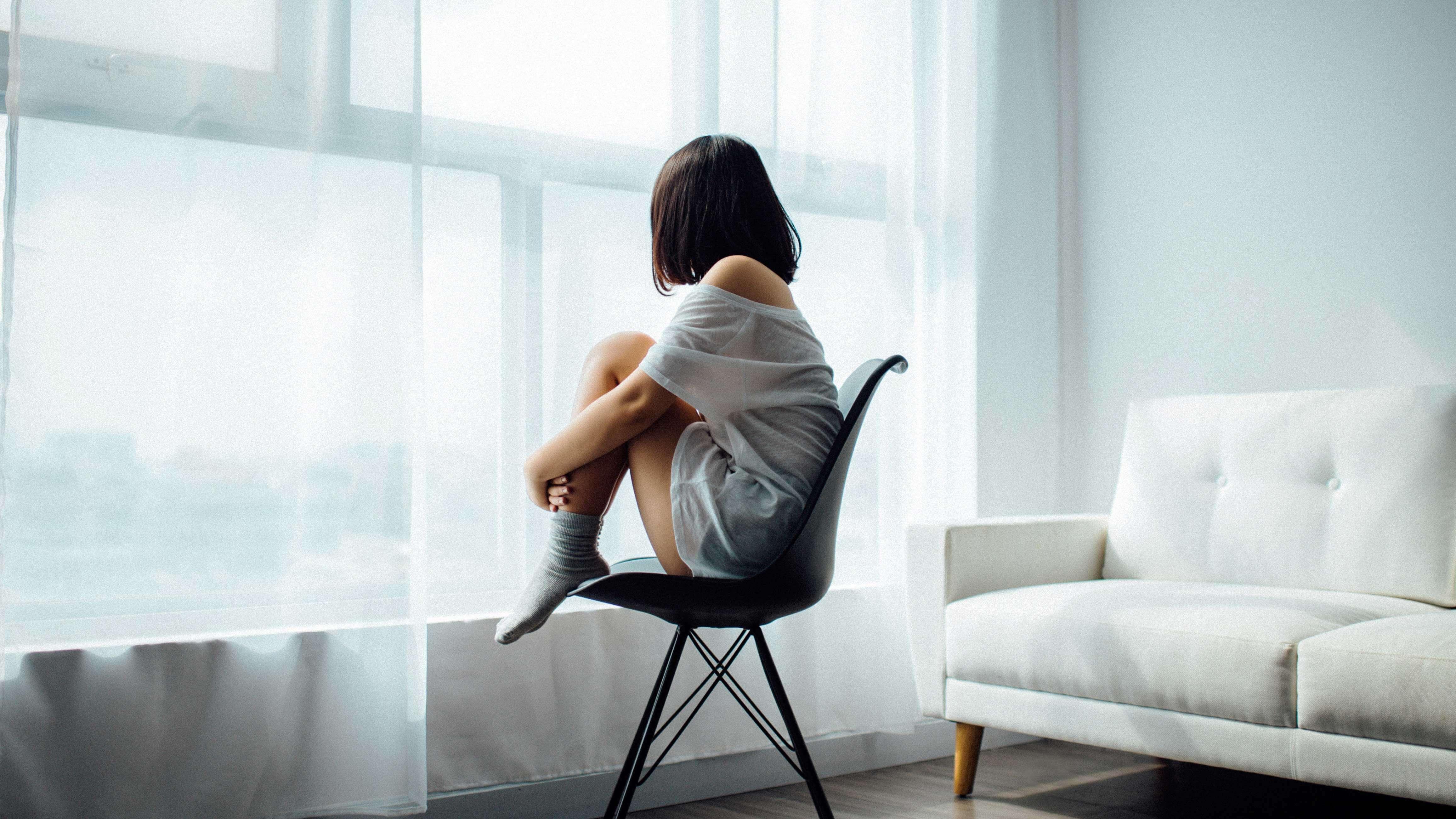 Reflexão: Sombras - Moça sentada em uma cadeira preta, o ambiente é uma sala branca com um sofá da mesma cor e uma janela.