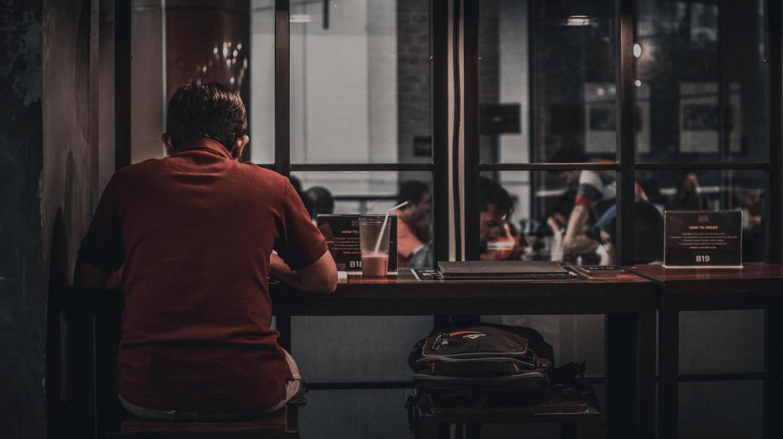 O cenário parece com o de uma cafeteria, temos um homem de costas usando uma camisa vermelha sozinho.