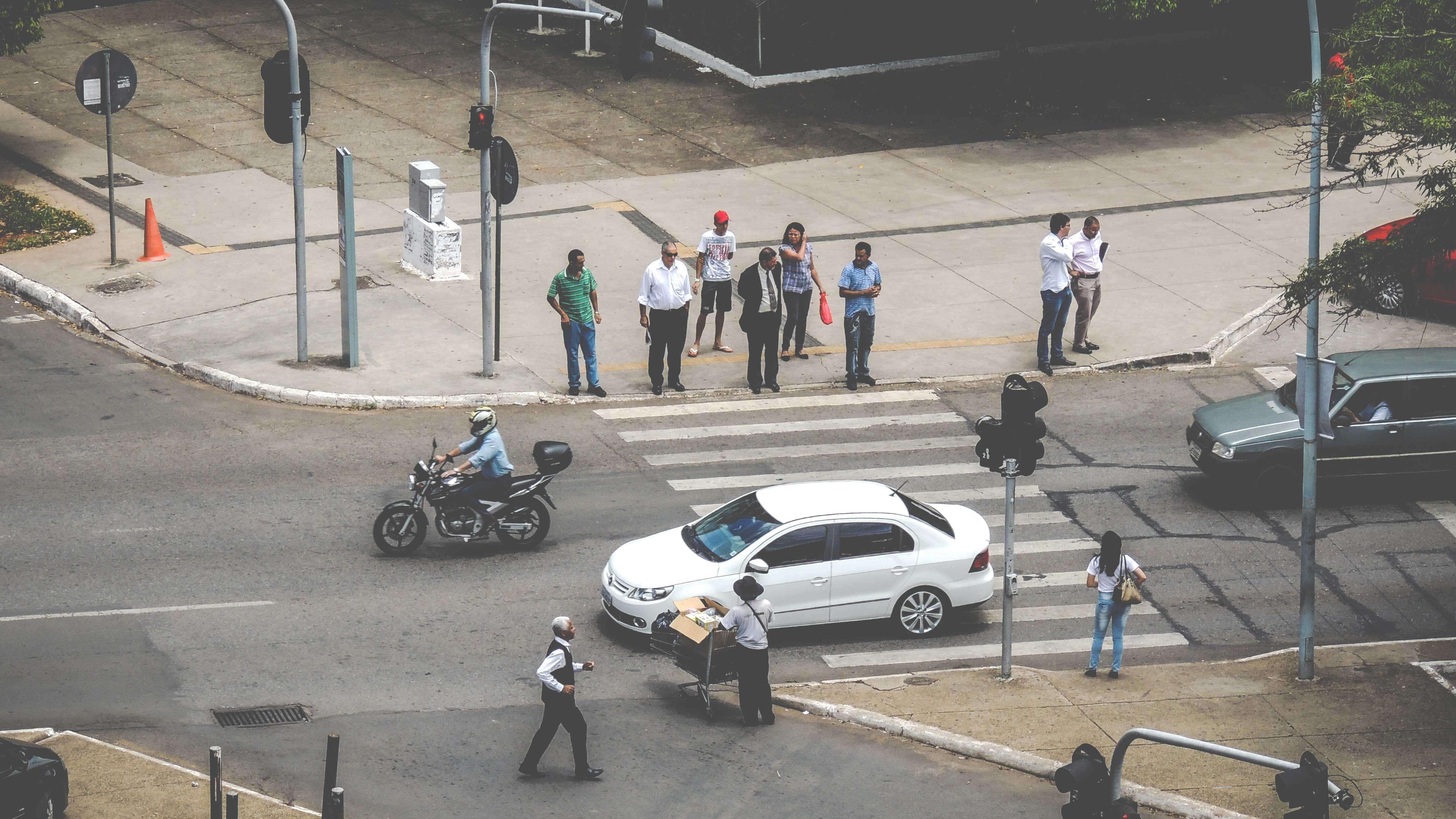 Rua vista de cima com pedestres aguardando para atravessar na faixa enquanto um carro branco passa.