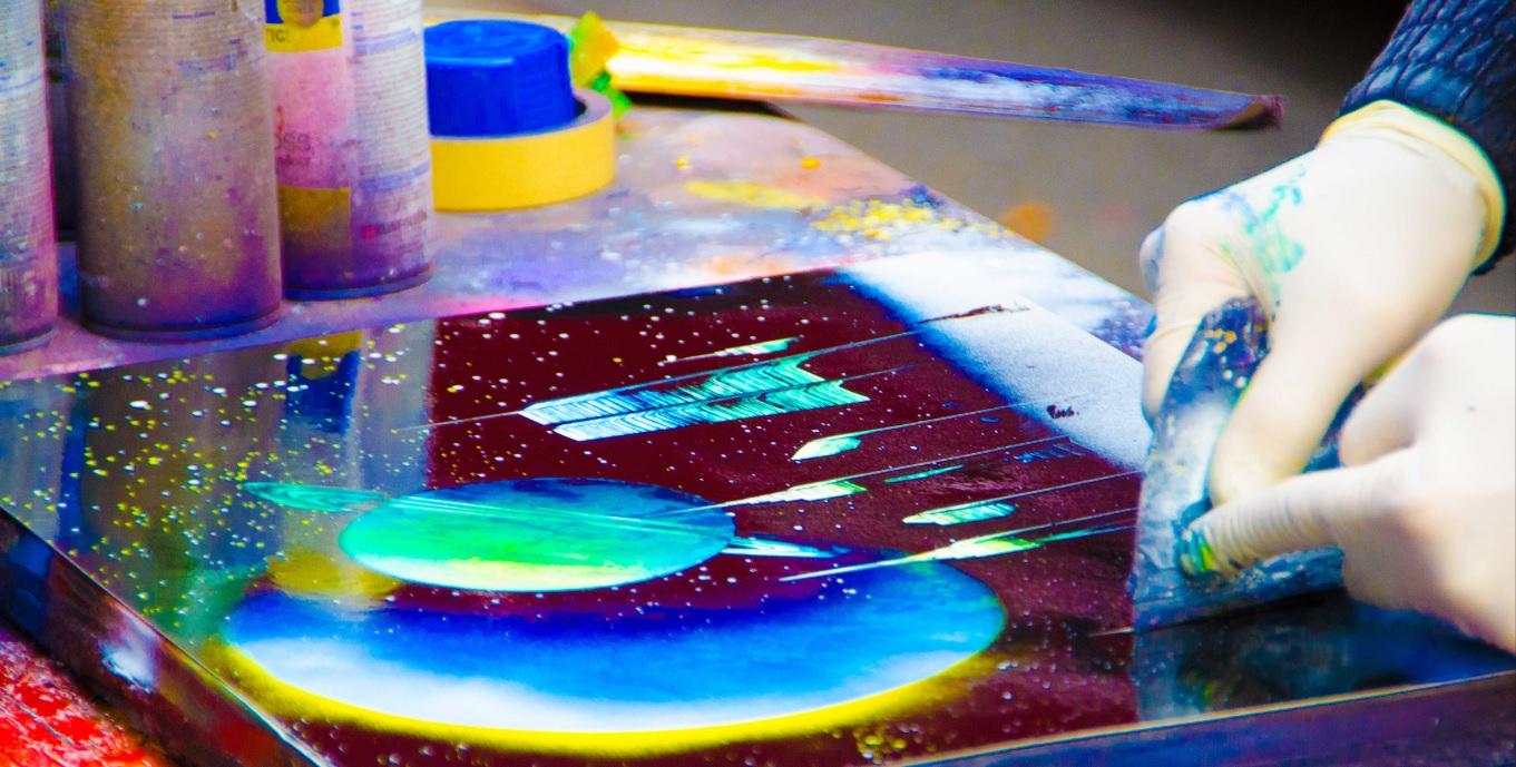 Artista pintando quadro que mostra os planelas com tinta spray.