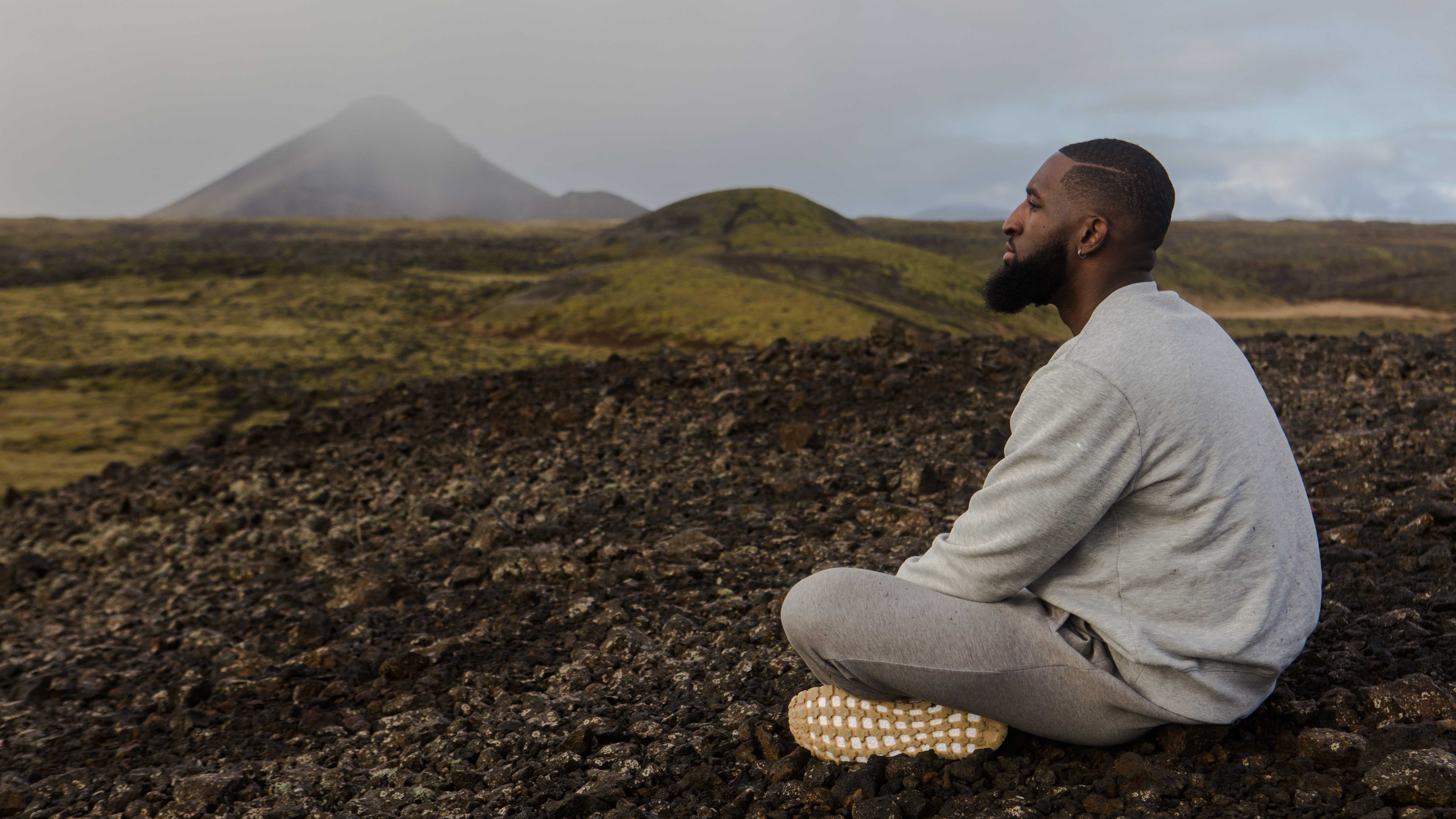 Homem meditando com montanhas atrás.