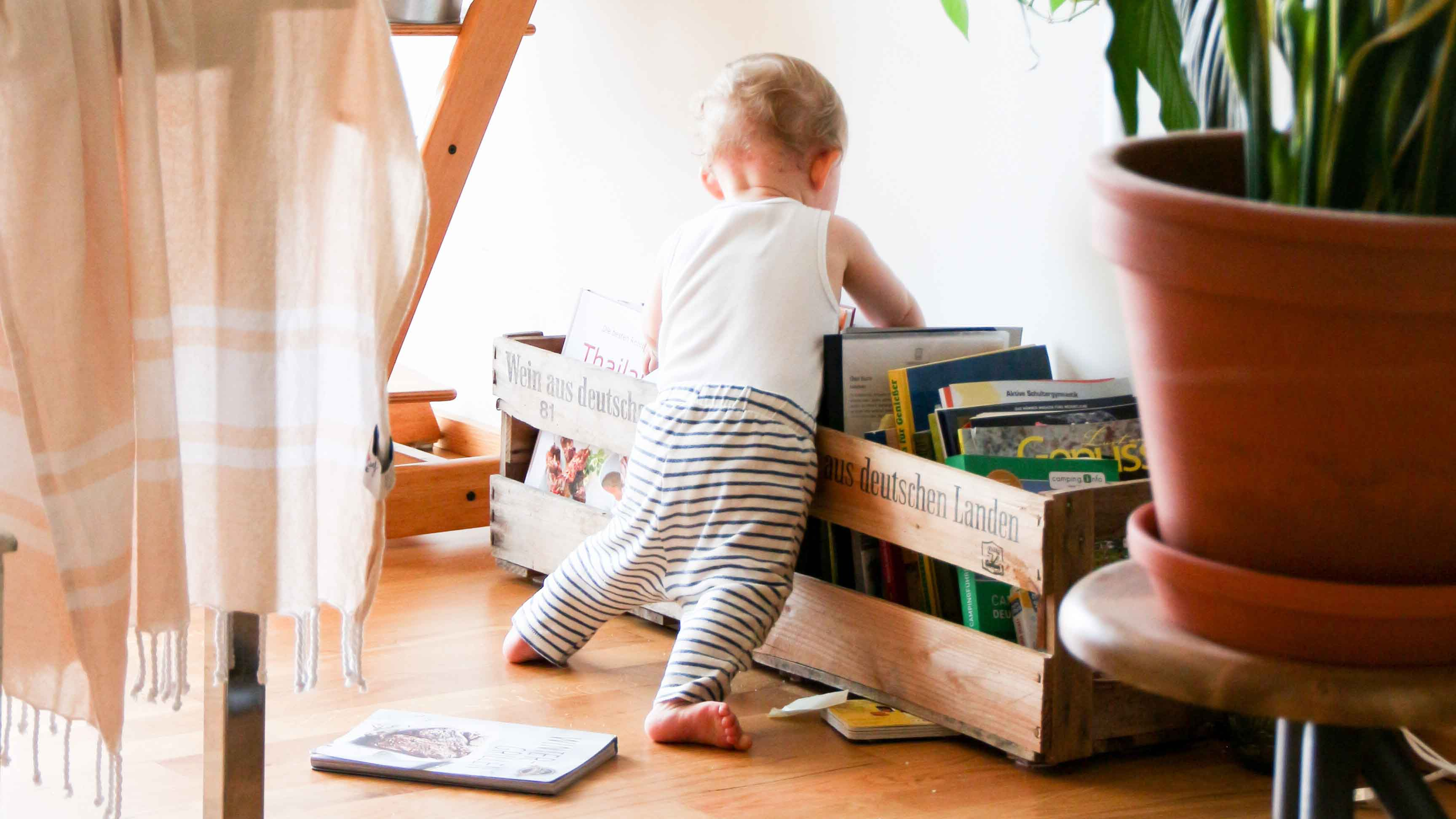 Bebe olhando livros em uma caixa no chão.
