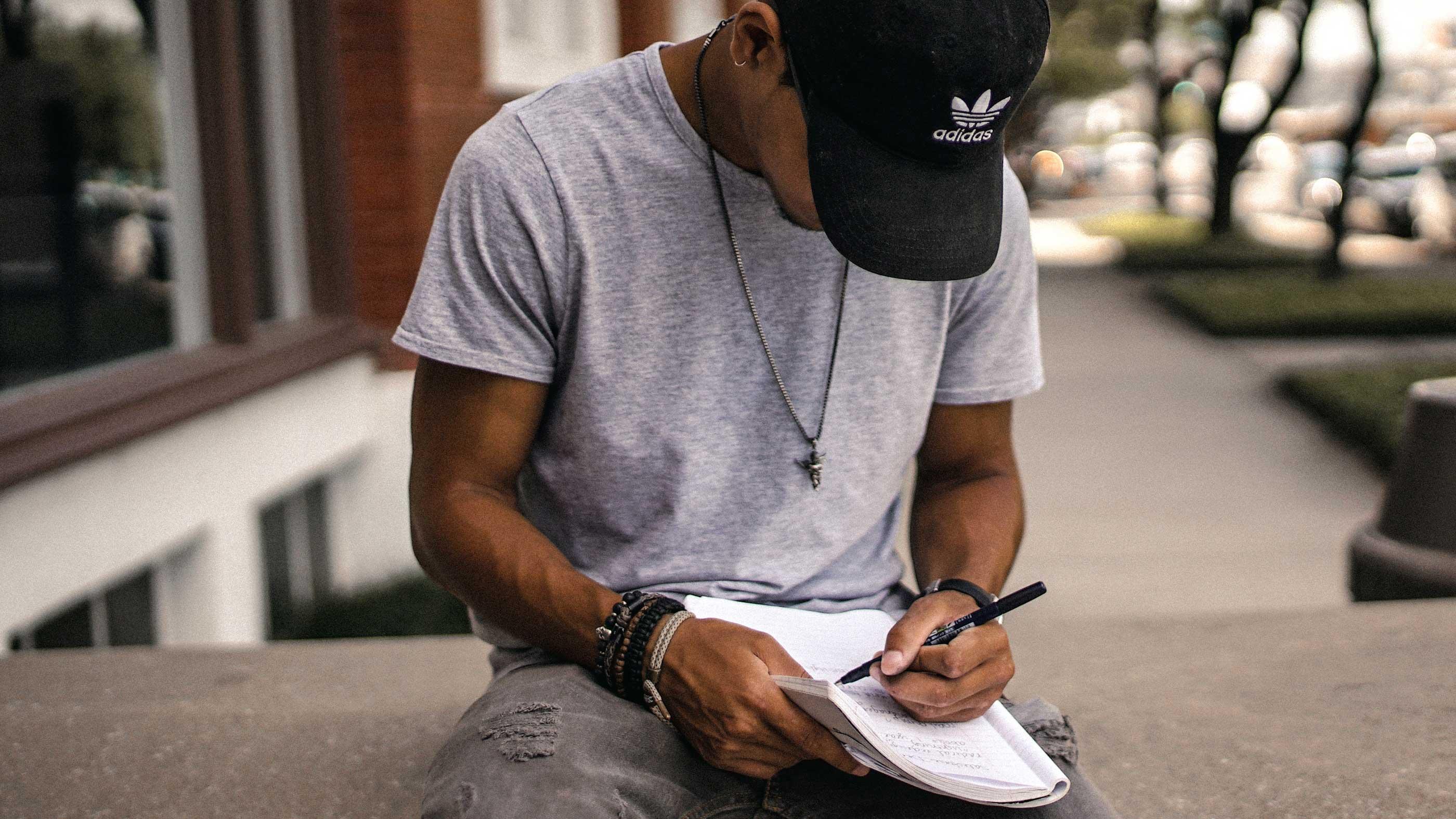 Rapaz sentado em mureta baixa escrevendo em seu caderno