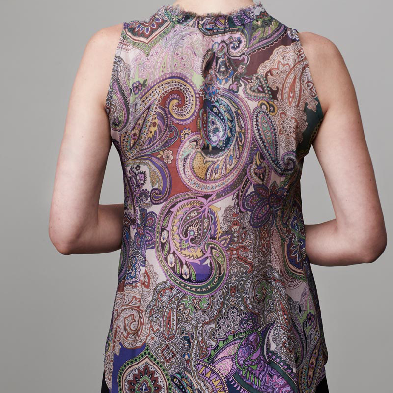 Back of model wearing paisley top