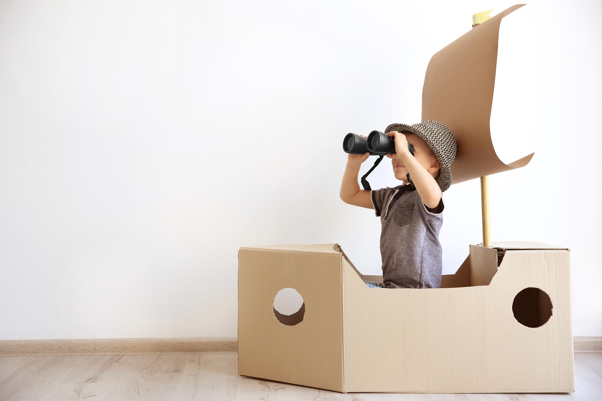 Boy in cardboard boat looking through binoculars
