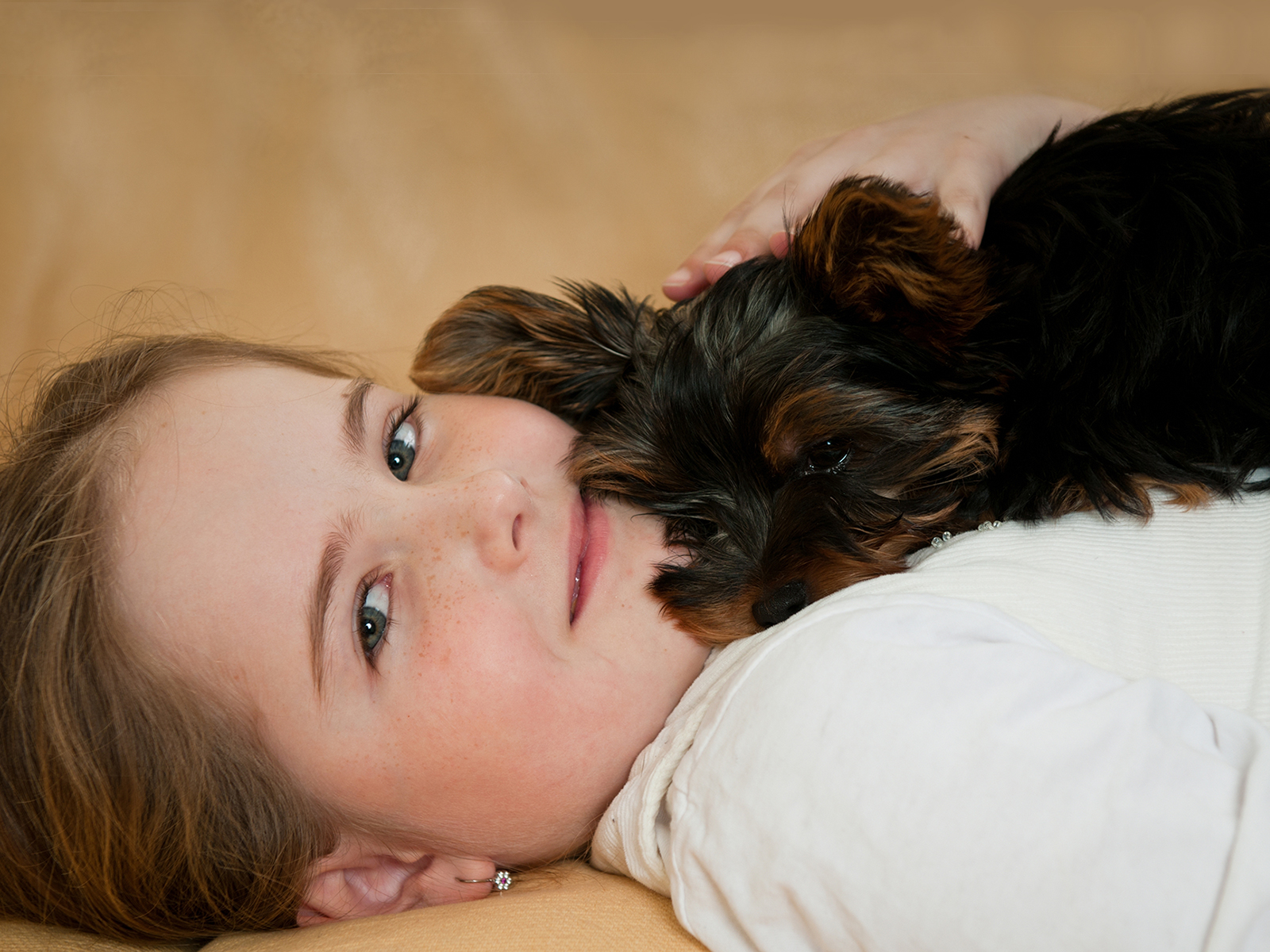 Cute young girl with her dog resting on her chest.