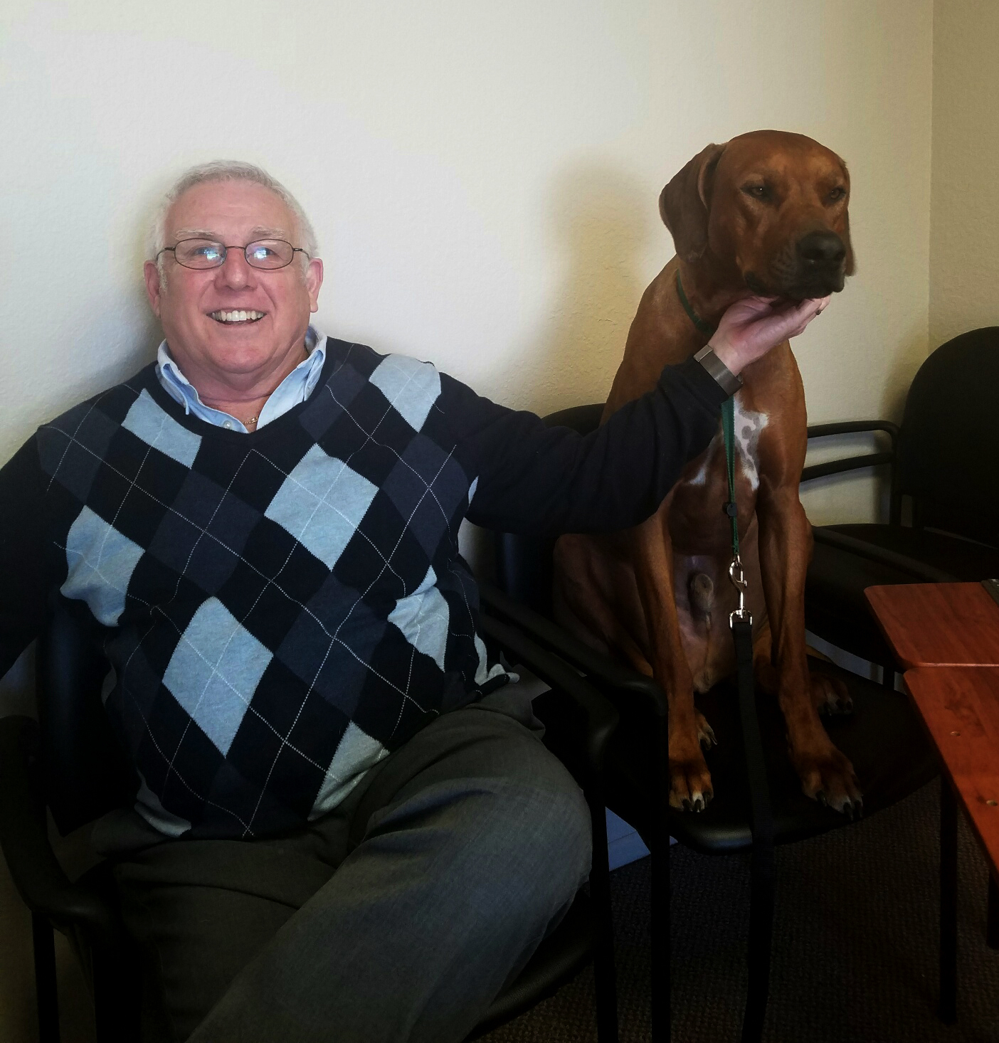Large dog sitting with Dr. Ken Tudor, veterinarian who developed the Healthier Homemade nutrient formulas and custom recipes