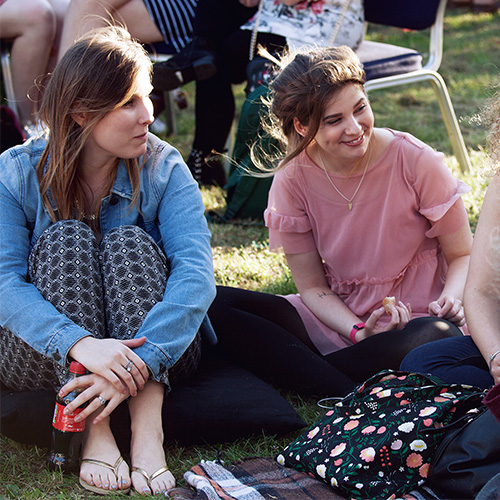 A group of young adult females sitting on a picnic blanket outside enjoying a conversation