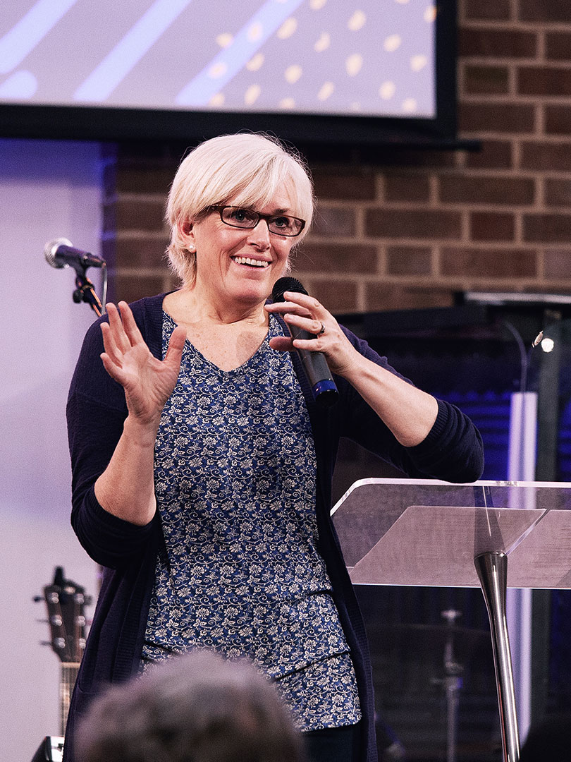 Ruth Poch preaching on a stage at regeneration Church during a Half Six service