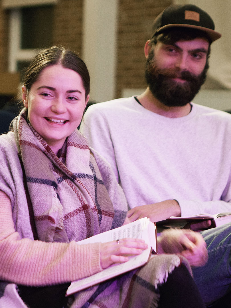 Two adults sitting next to each other and laughing while holding a Bible each on their laps at Charcoal
