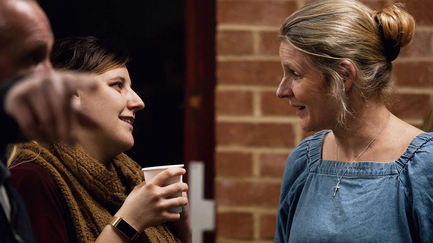 One woman chatting with another while holding a cup of coffee in the Welcome Lounge at regeneration Church