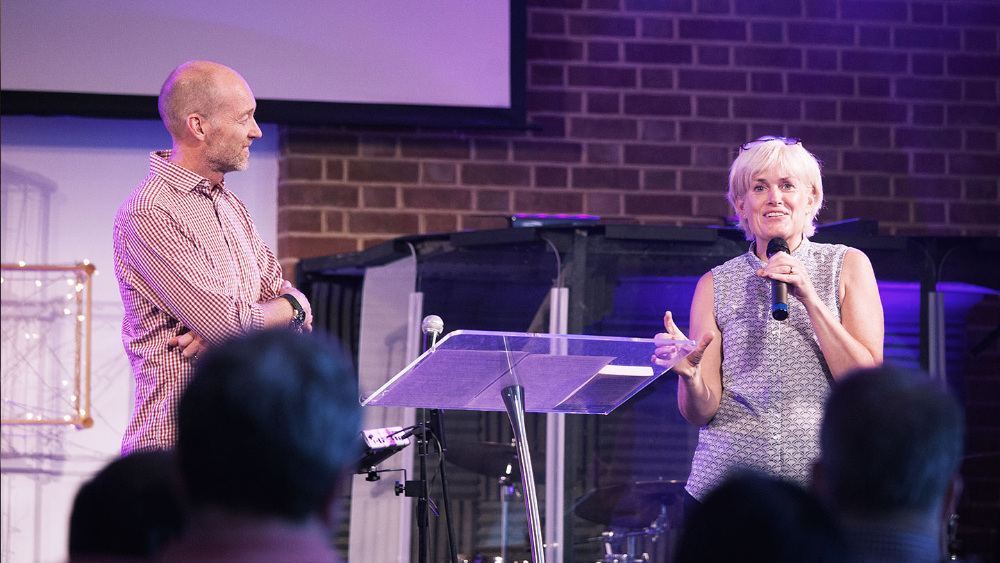 James Poch listening to Ruth Poch share with a microphone, while both are on the platform, at regeneration Church