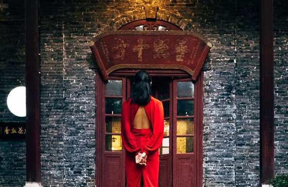 Woman looking onto a traditional Chinese tea house