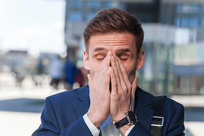 Young man rubbing his face with both hands because of sinus pressure.