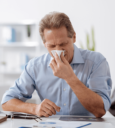Man sitting at desk wiping his nose due to possible nasal polyp symptoms.