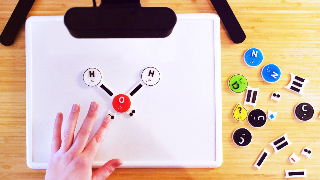 Top down image of the Kasi set up showing the camera pointed down at the magnetic white board with the atom, bond, lone pair, and charge pieces on the table. The Water molecule is being put together on the white board.
