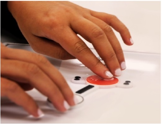 Image of a pair of hands touching Kasi's tactile pieces. These pieces have extruded letters and braille on them for students to feel.