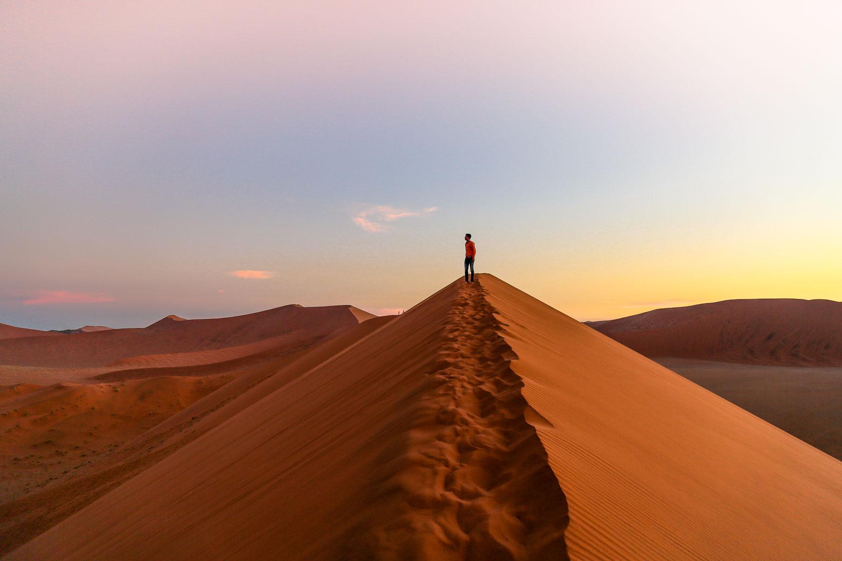 Ein Mann steht auf einer Düne in der Wüste von Namibia.