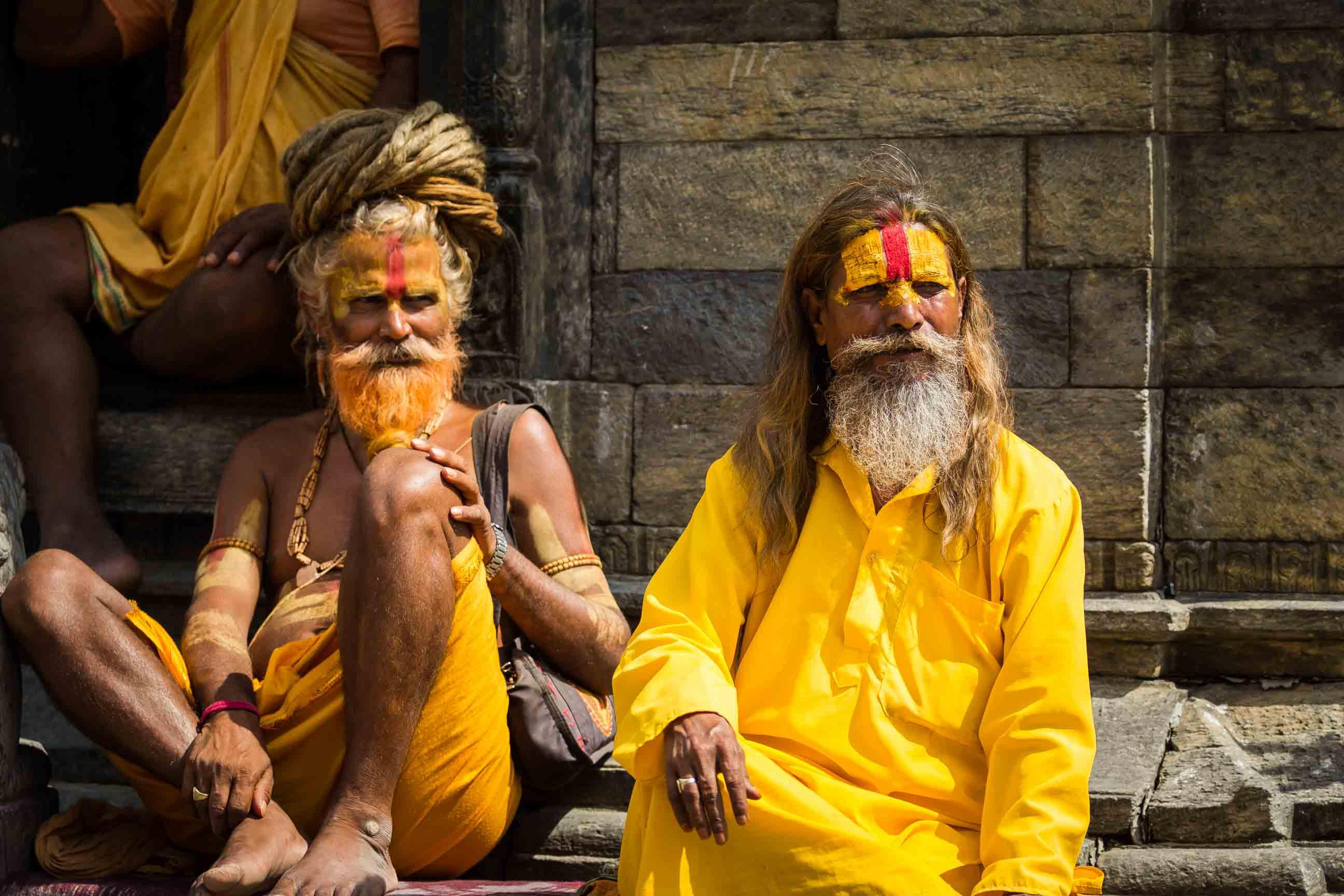 Zwei hinduistische Männer sitzen vor einem Tempel in Nepal.