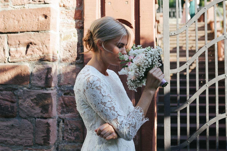 Die Braut riecht an ihrem Blumenstrauß.