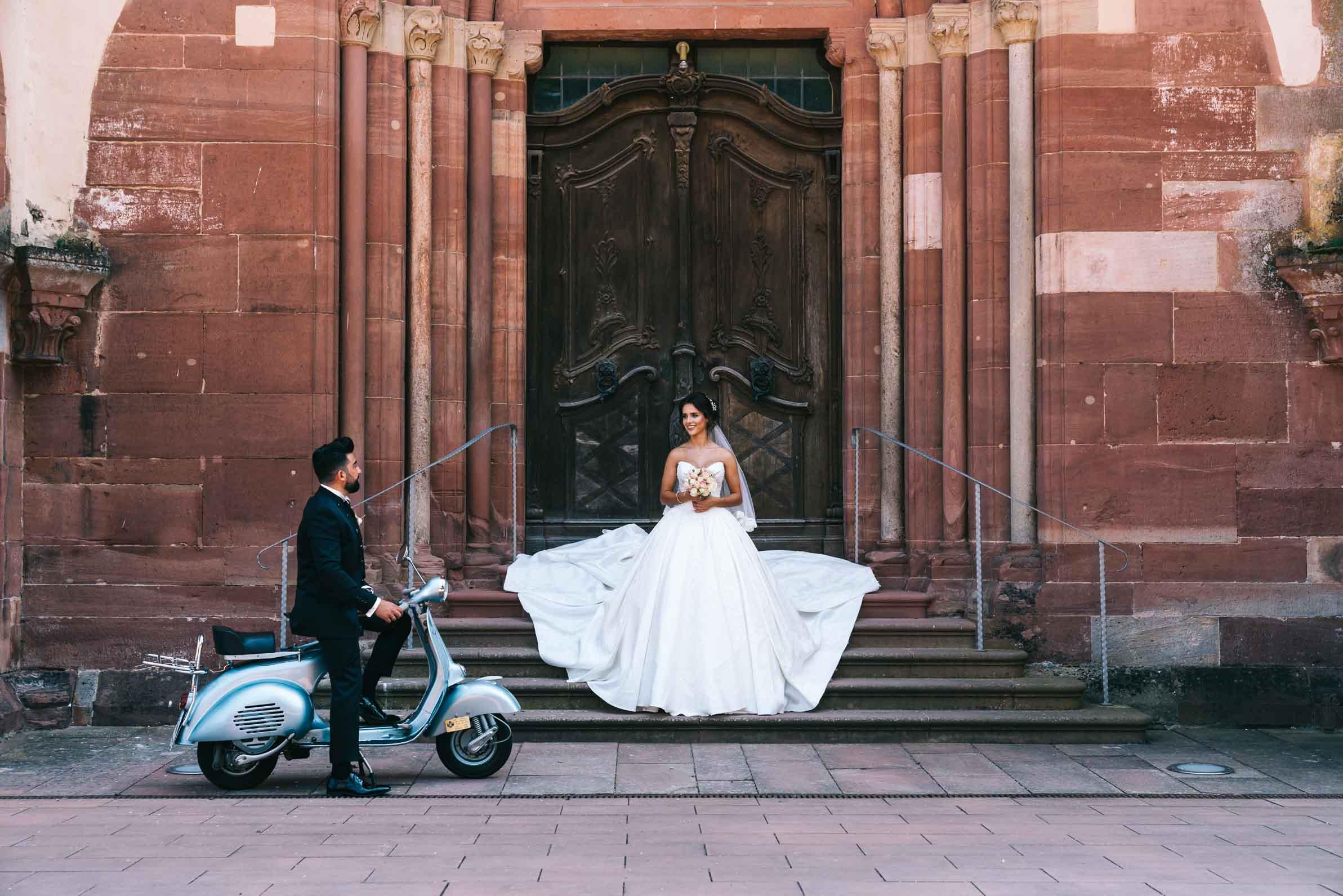 Der Bräutigam holt seine Braut mit einer blauen Vespa ab.