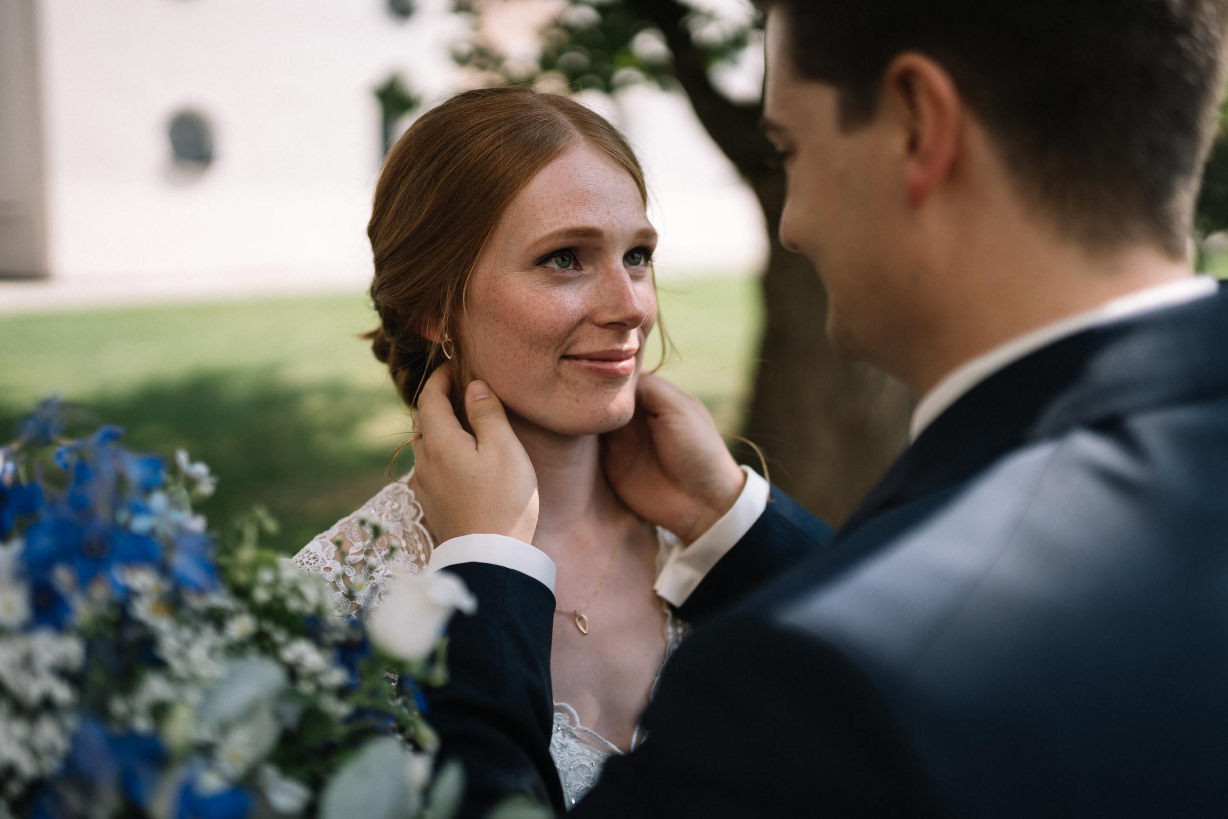 Der Bräutigam hält den Kopf der Braut.