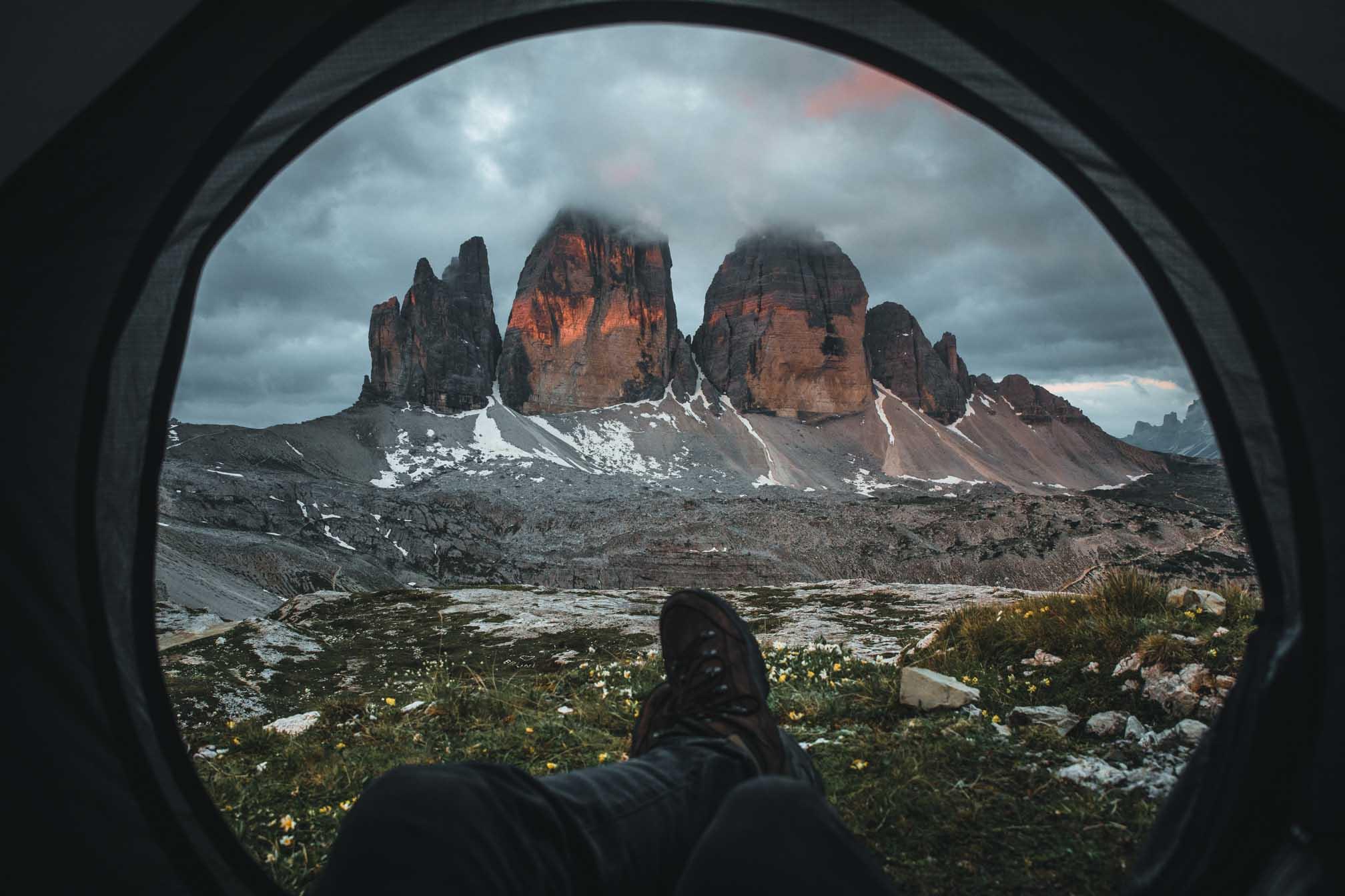 Der Blick auf die Drei Zinnen aus einem aufgeschlagenen Zelt.