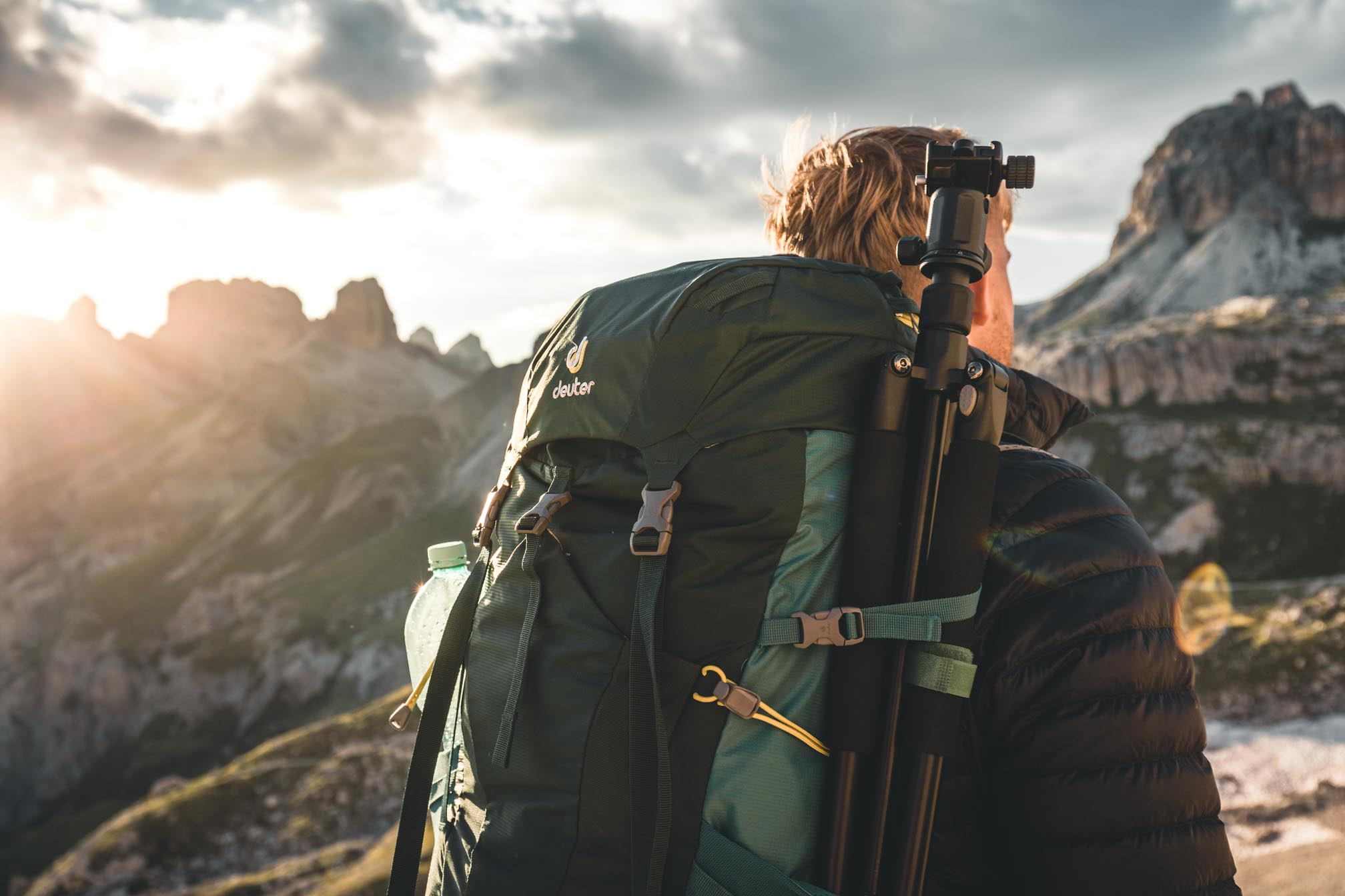 Ein Mann mit Rucksack wandert einen Berg hinauf.