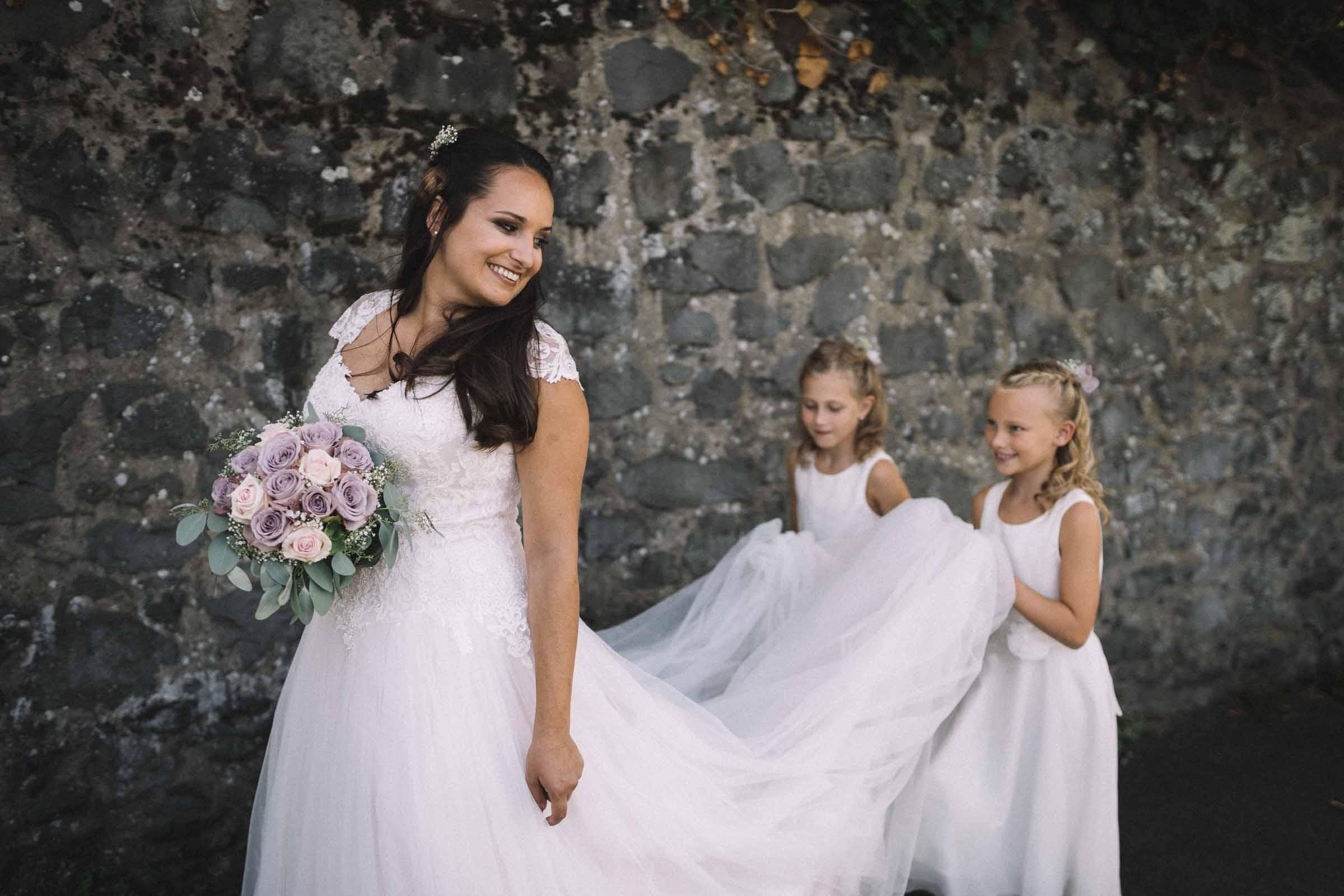 Zwei Blumenmädchen halten die Schleppe der Braut.