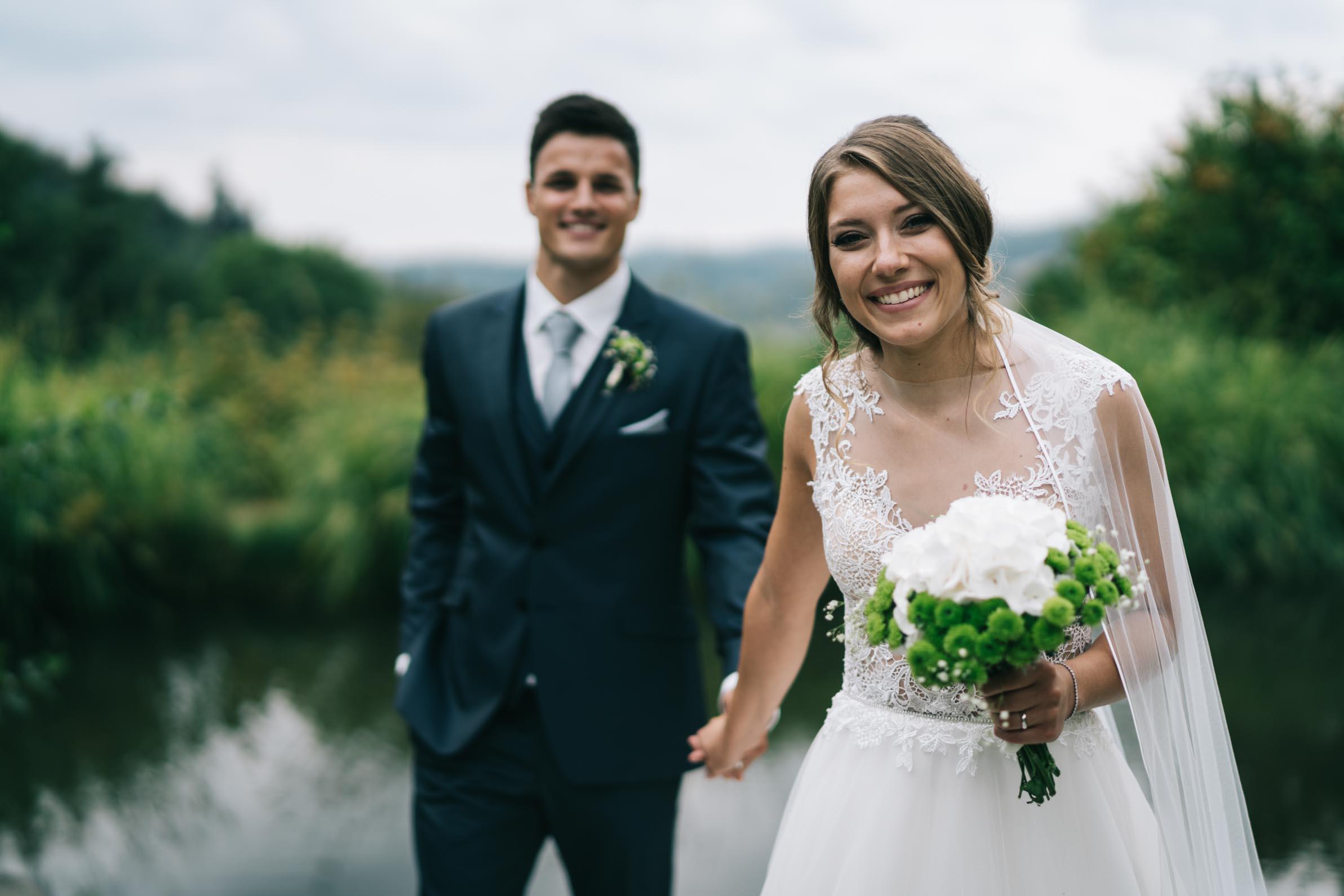Das Brautpaar geht Hand in Hand auf einem Steg.