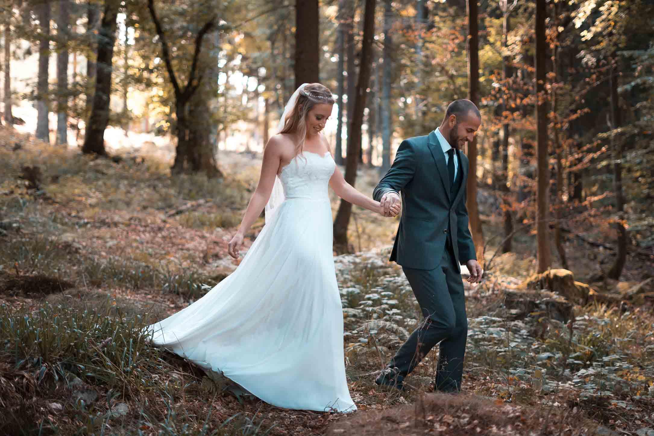 Das Brautpaar läuft Hand in Hand durch einen Wald.