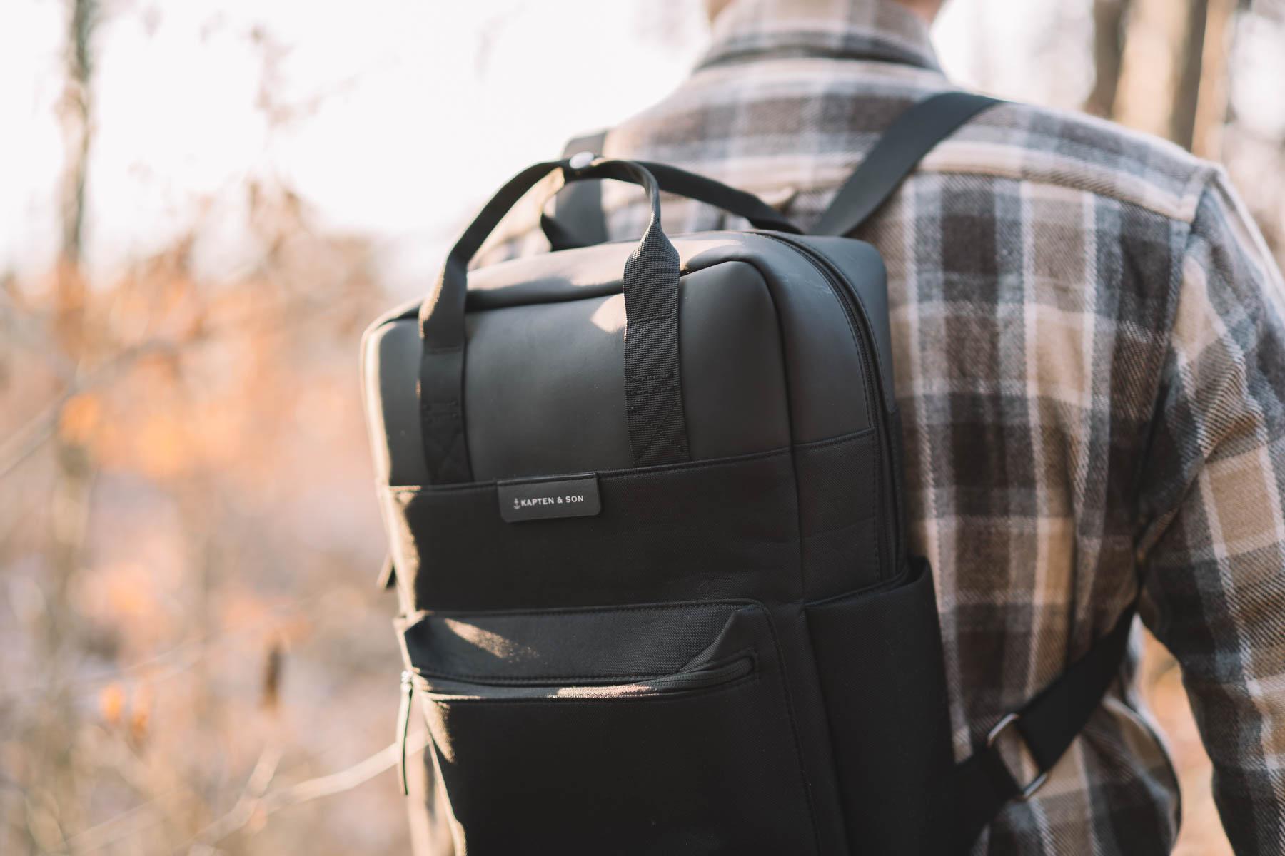 Ein Mann trägt einen Rucksack im Wald.
