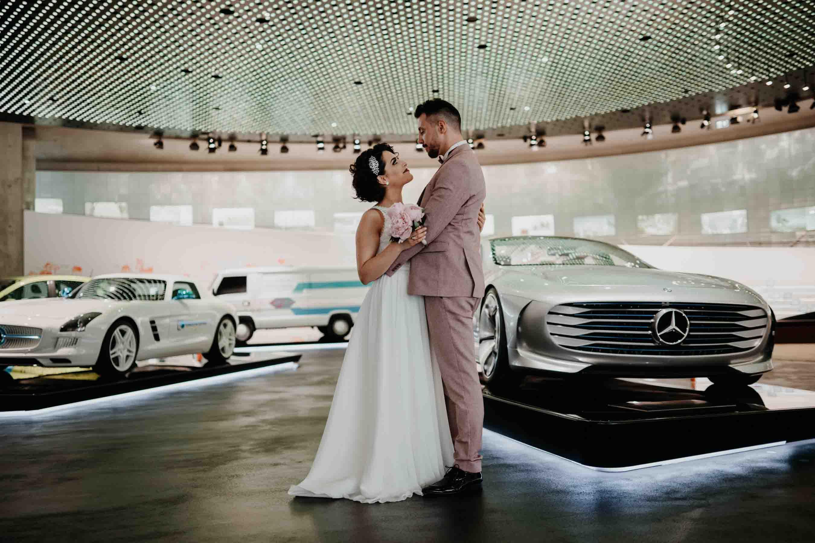 Das Brautpaar posiert zusammen im Mercedes Benz Museum.