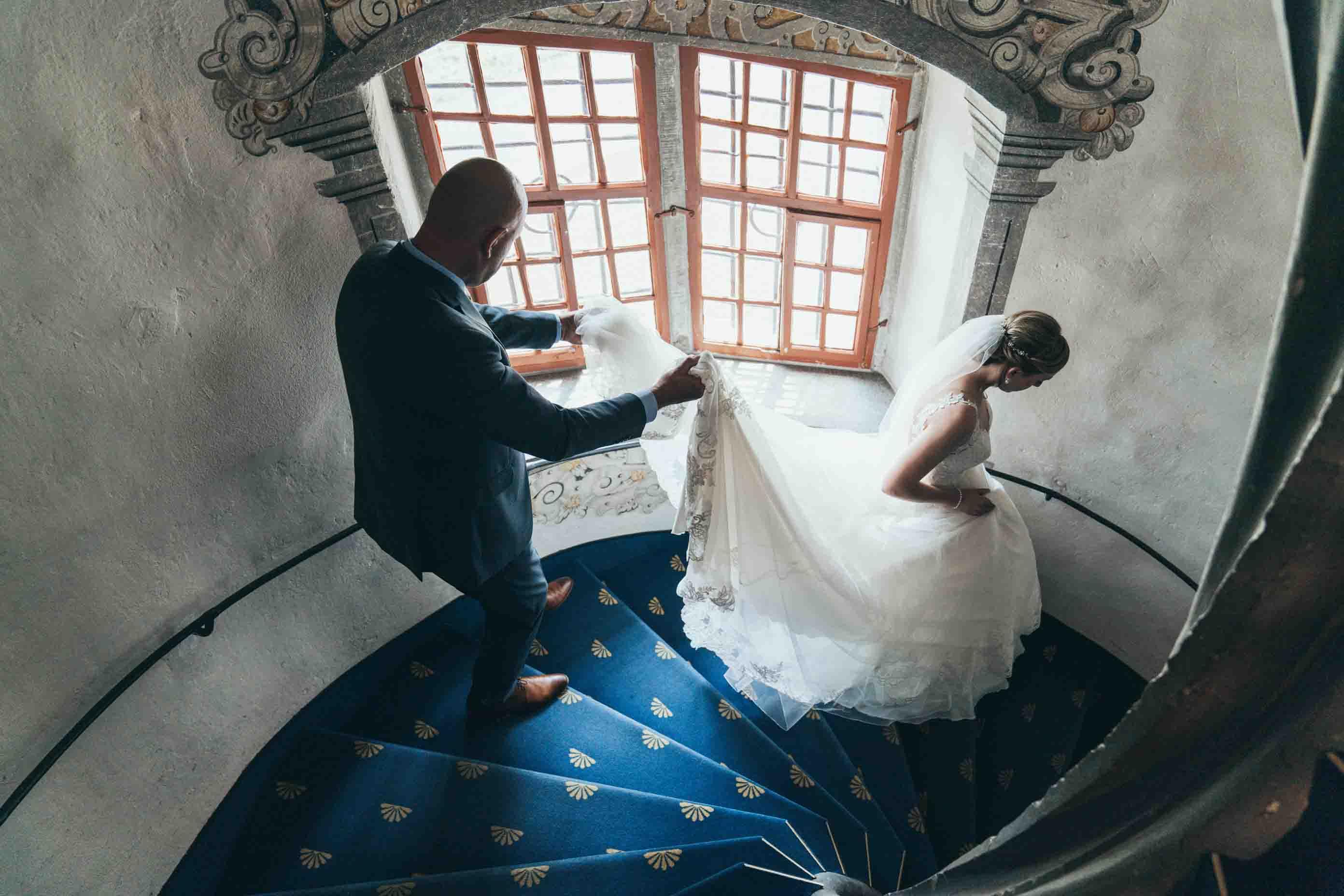 Der Vater führt die Braut die Treppe hinunter und hält dabei ihren Schleier.
