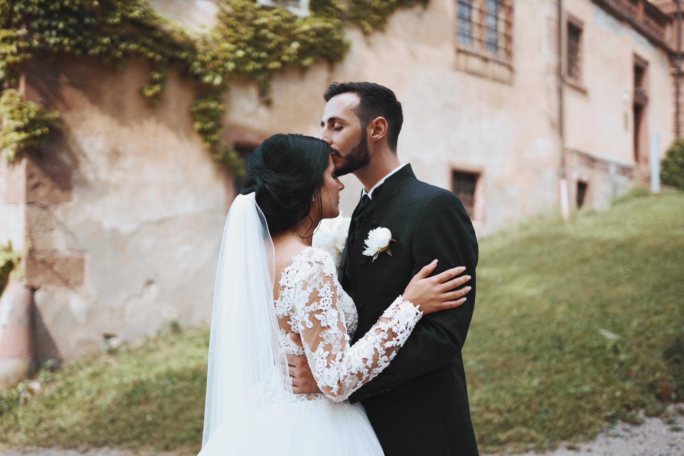 Der Bräutigam küsst seine Braut liebevoll auf die Stirn.