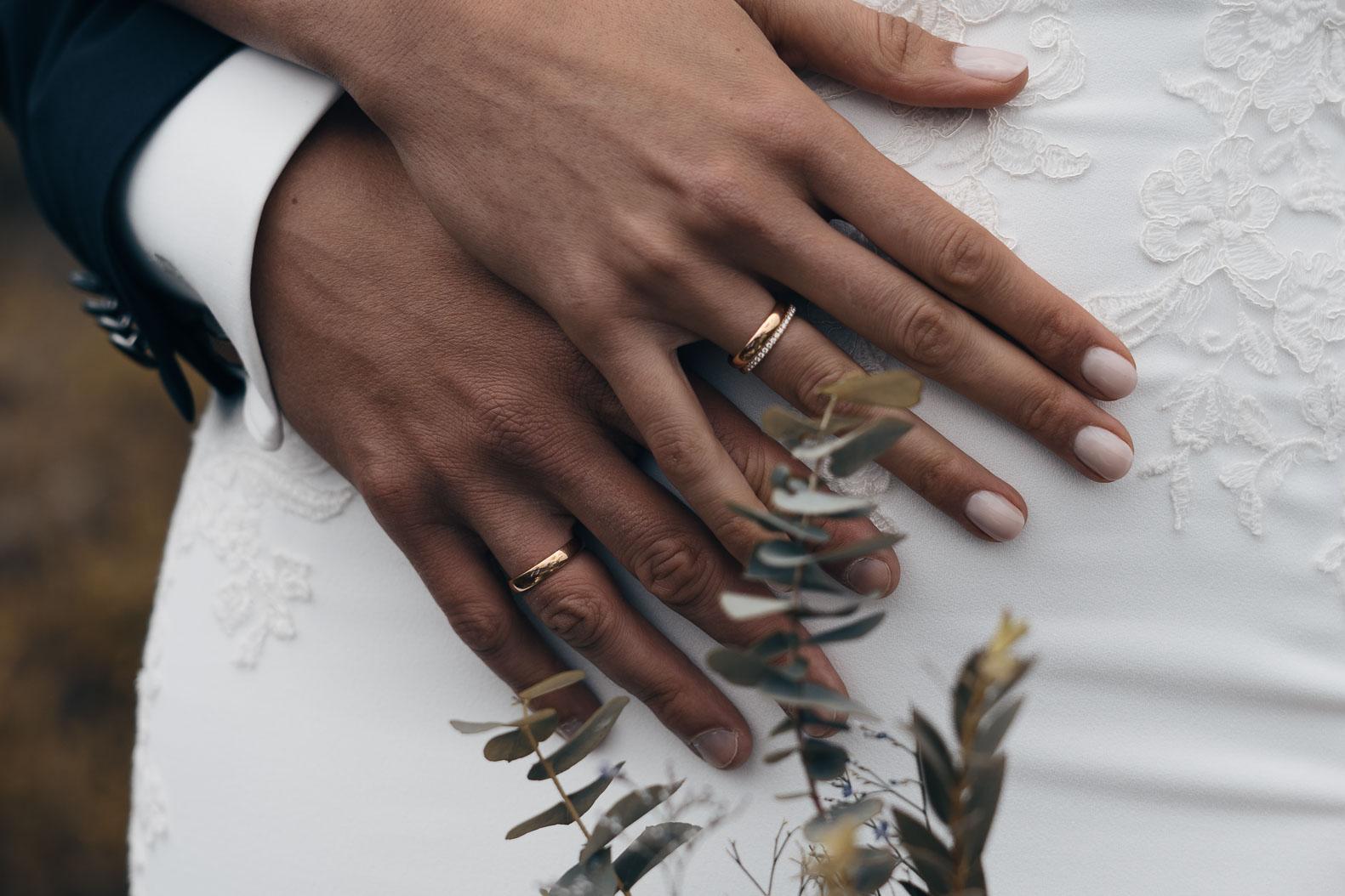 Eine Nahaufnahme der Hände von Braut und Bräutigam.