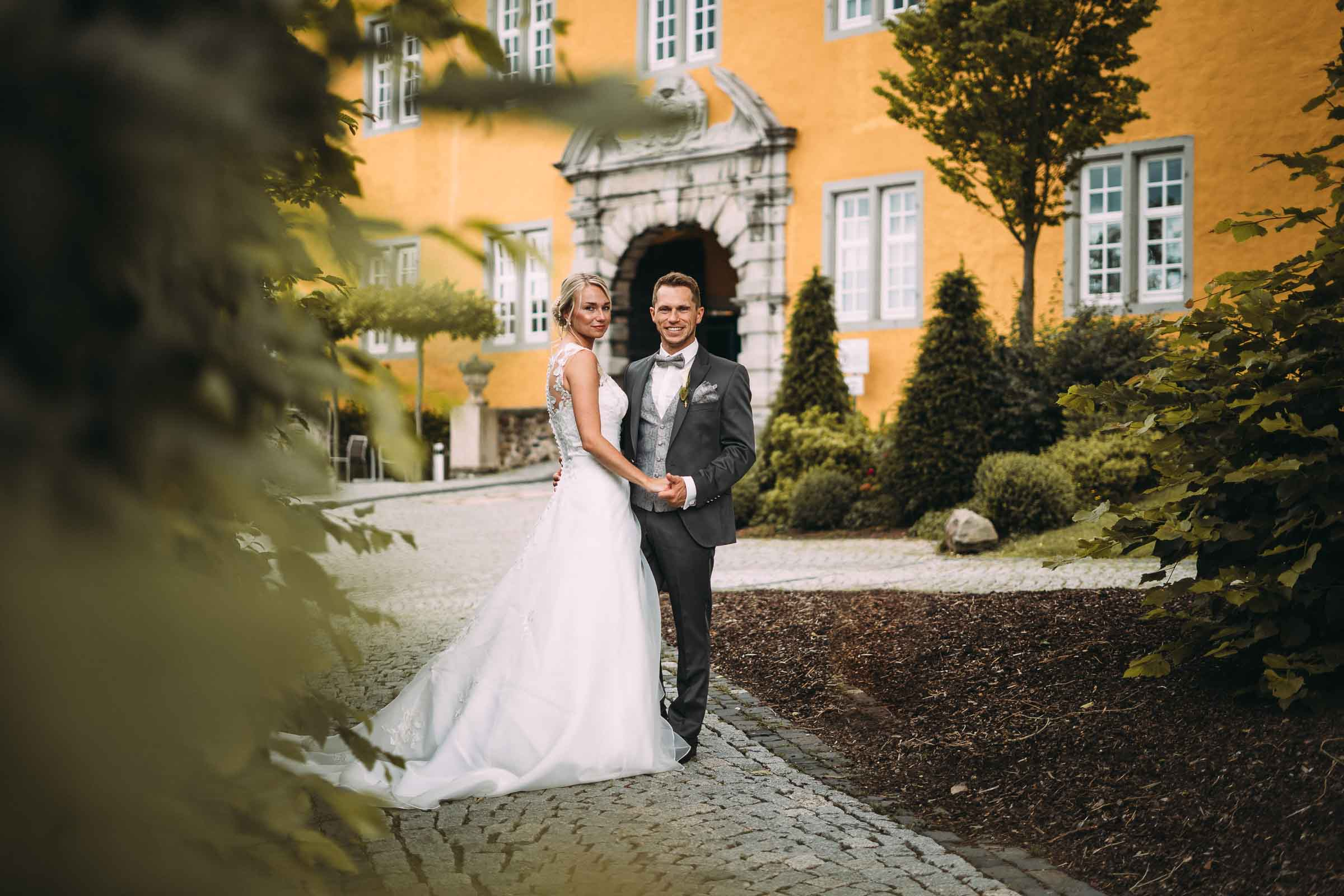 Das Brautpaar posiert vor einem Schloss.