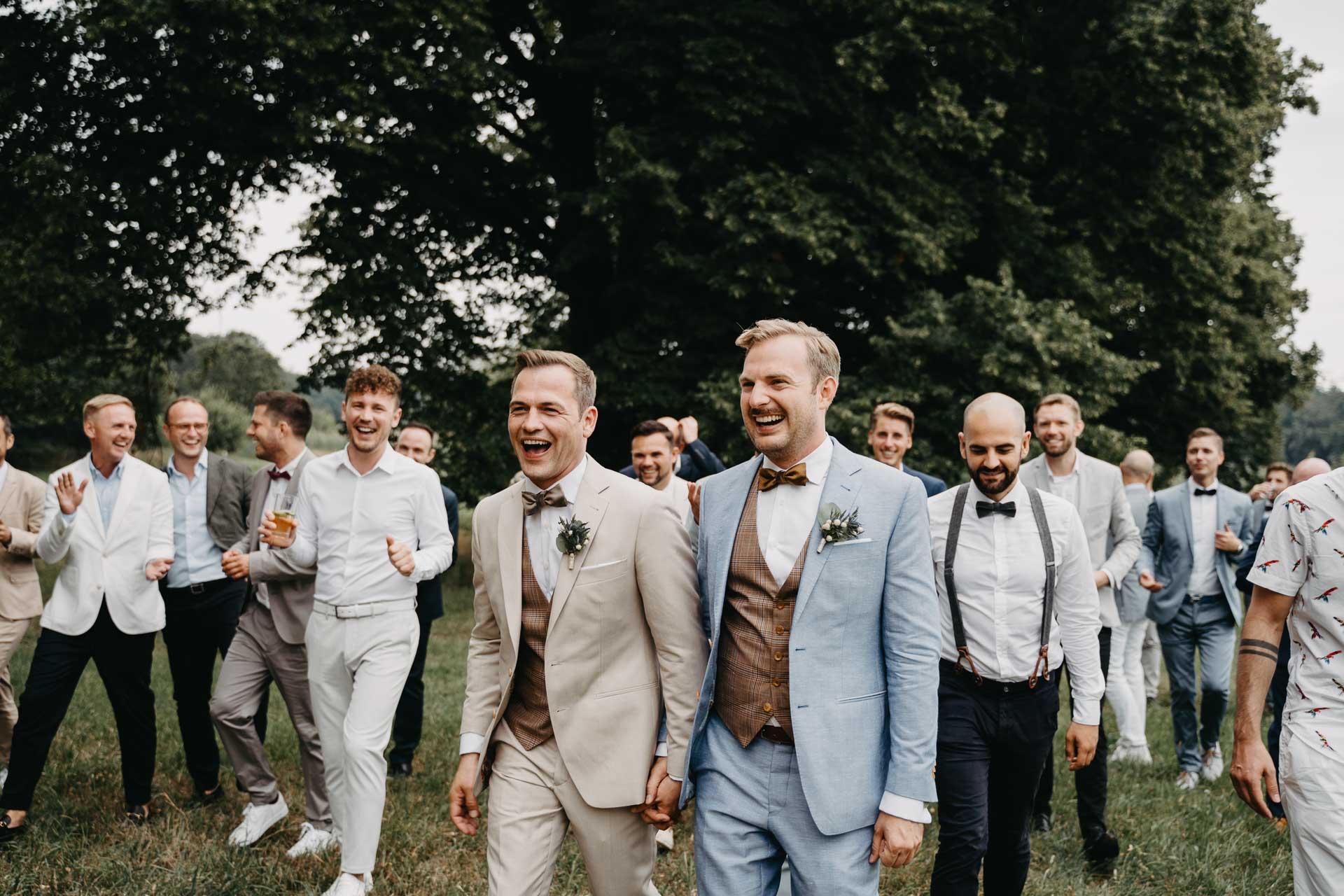 Das Brautpaar läuft umringt von Gästen über eine Wiese.