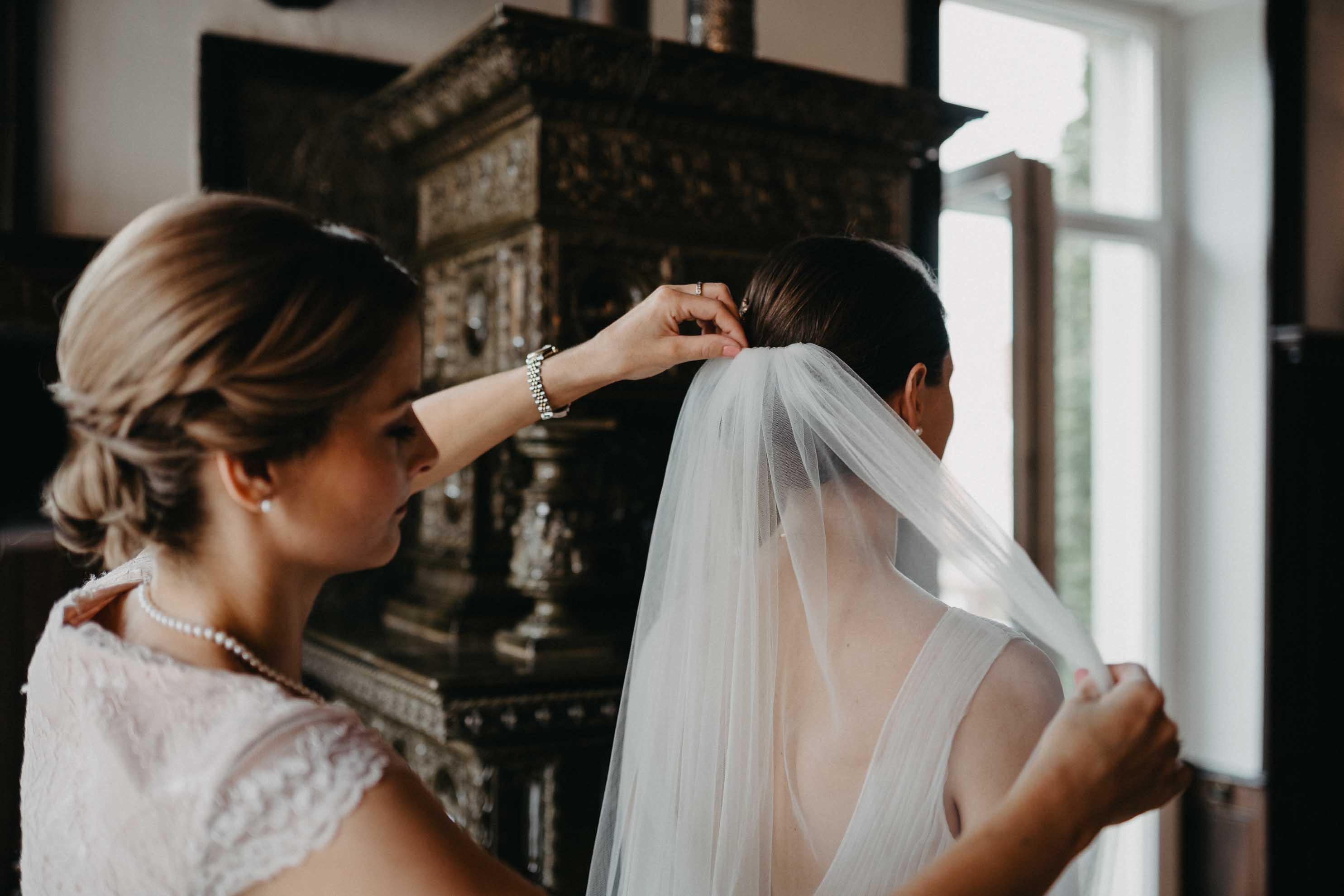 Der Braut wird ihr Schleier angesteckt.
