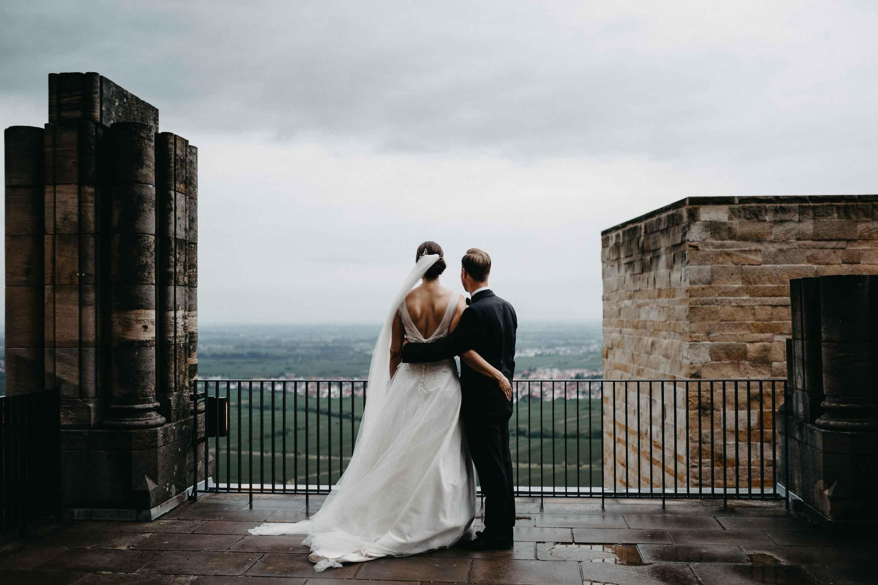 Das Brautpaar blickt von einem Schloss in die Ferne.