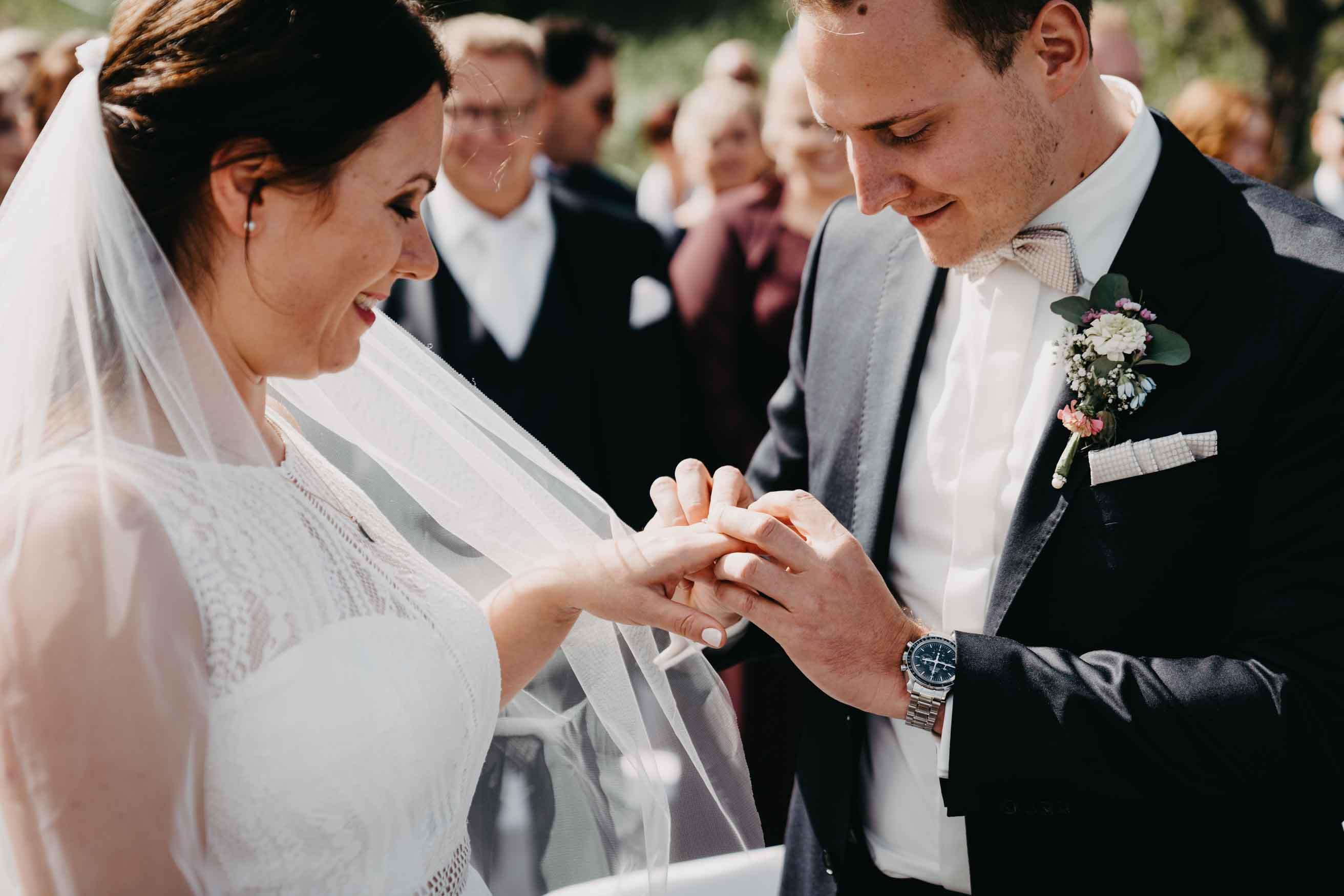 Der Bräutigam steckt seiner Braut den Ring an.