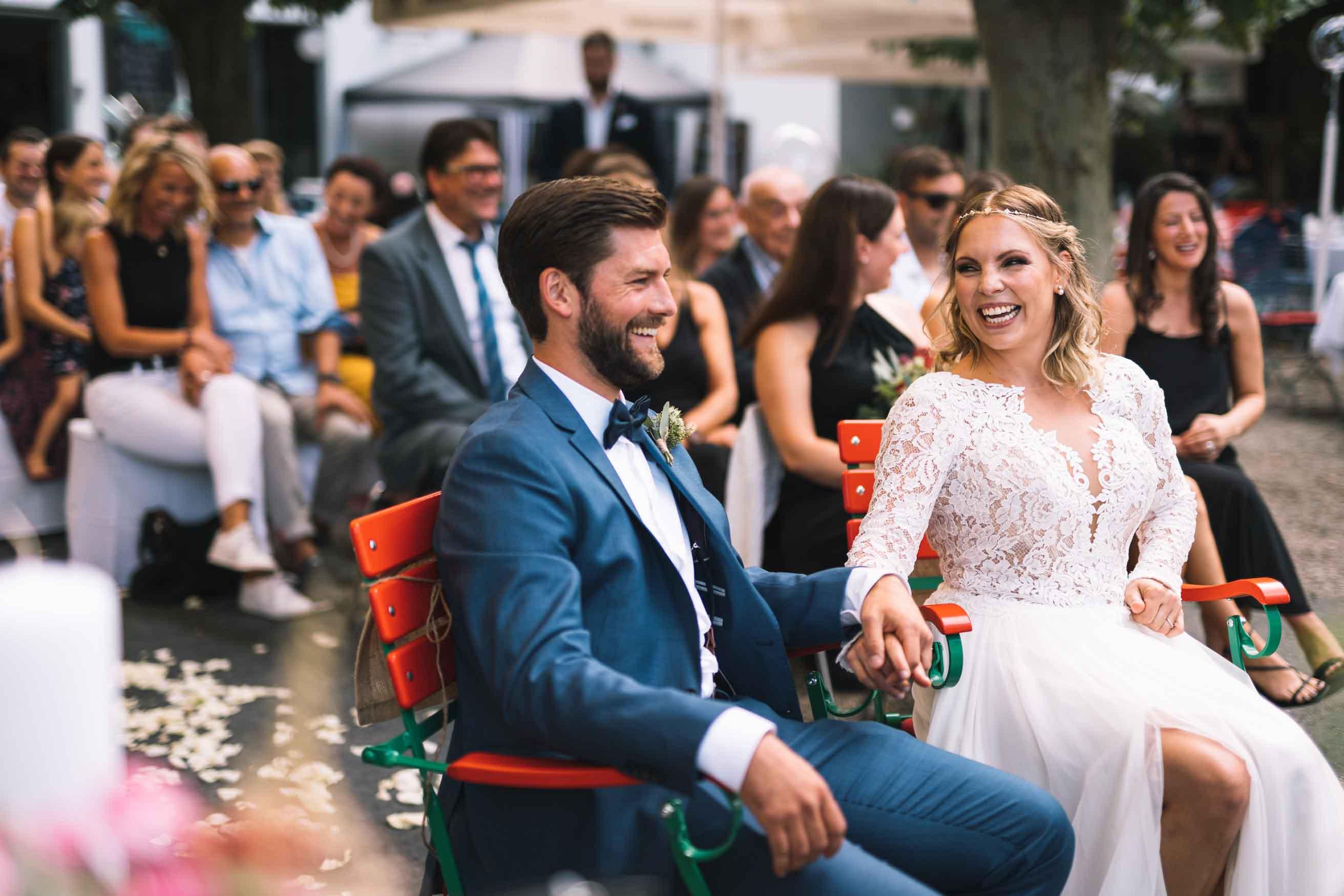 Das Brautpaar sitzt vor den Gästen und lauscht der Traurede.